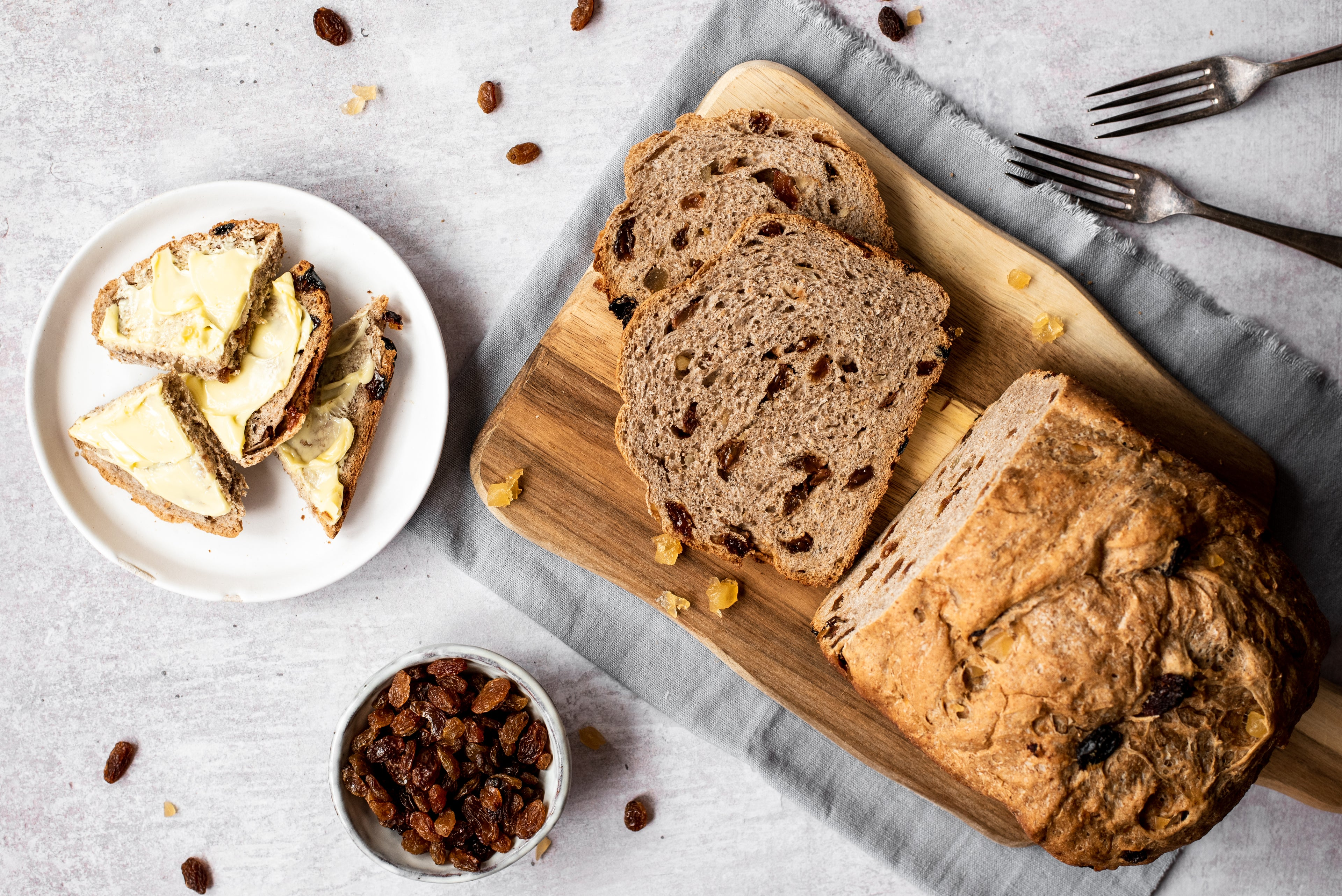 Overhead of fruit bread with slices cut. Plate with buttered slices. Bowl of sultanas. Two forks