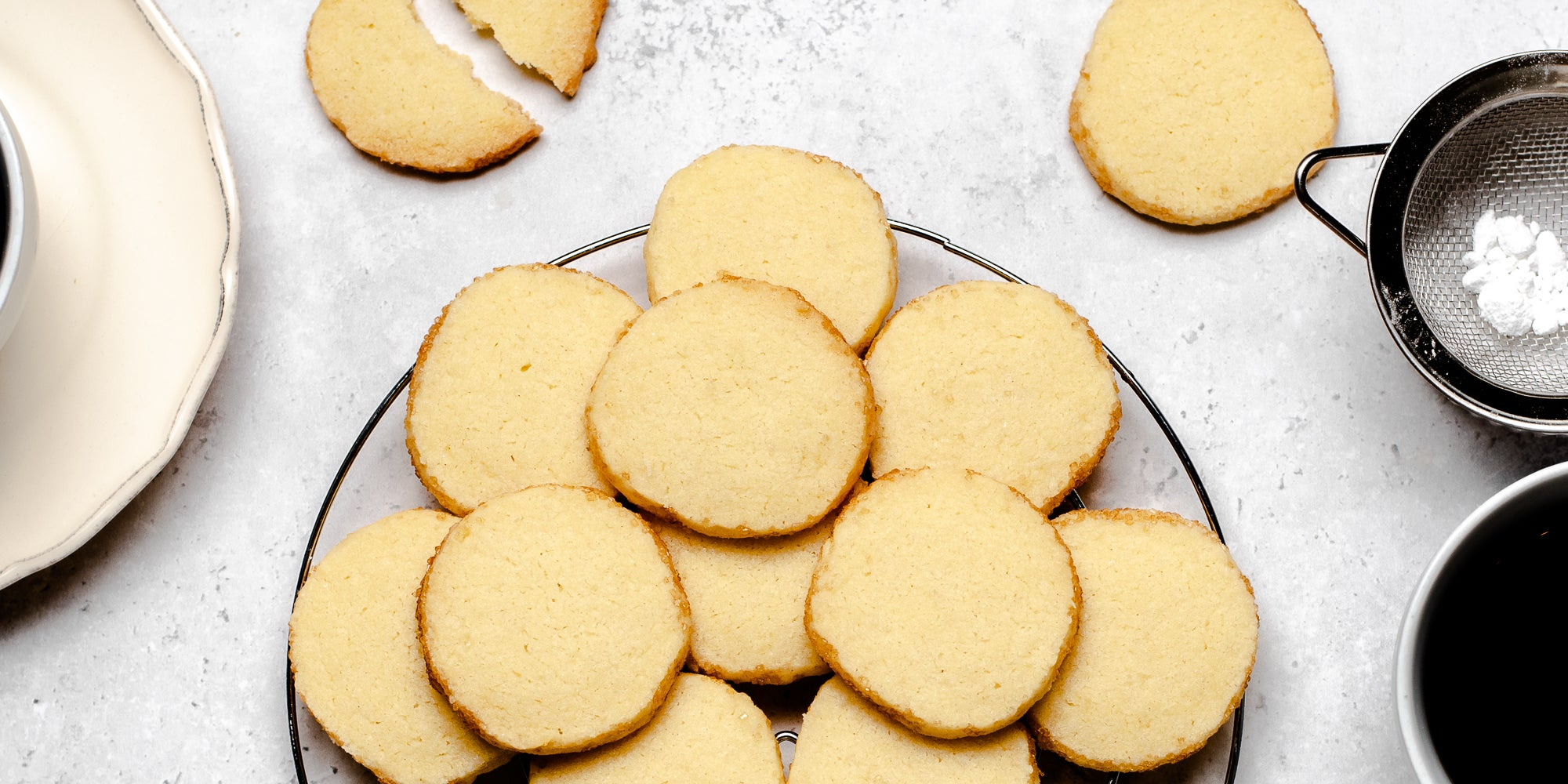 A batch of baked Shortbread Dough biscuits on a plate, next to a sieve