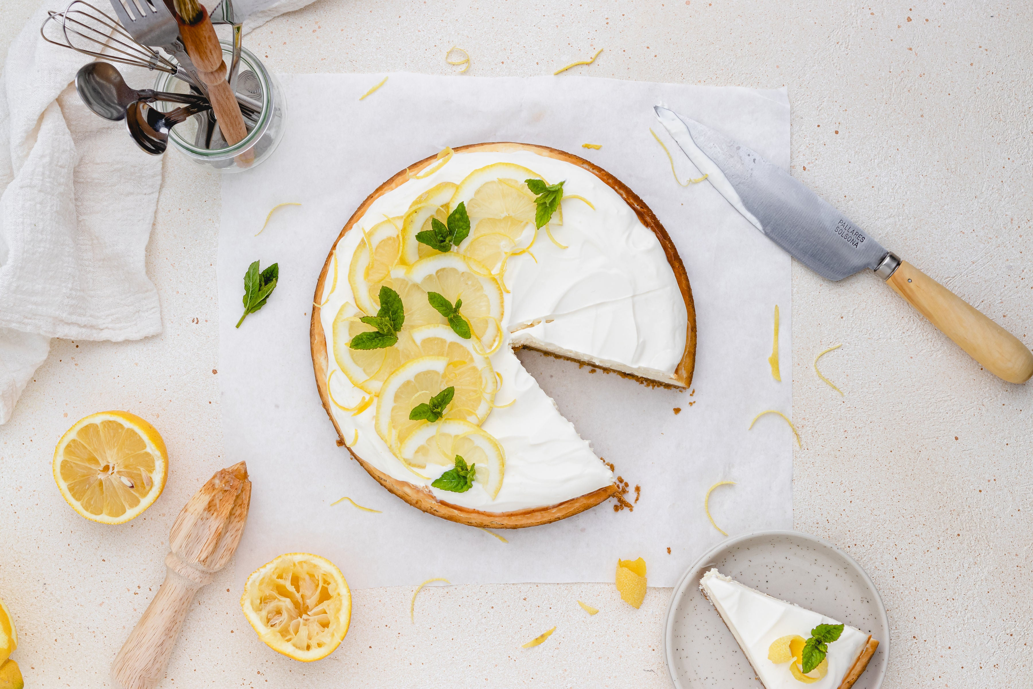 Overhead shot of cheesecake with lemon slices and a slice removed