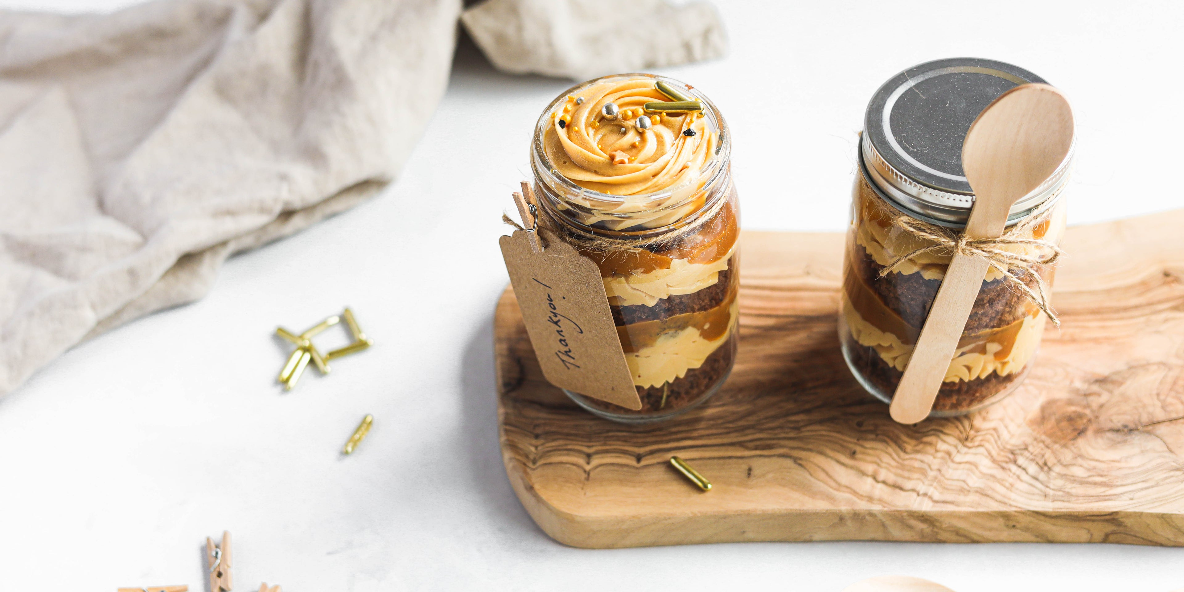 Chocolate & Salted Caramel Cupcakes in a Jar on a serving board with sprinkles and a handwritten note