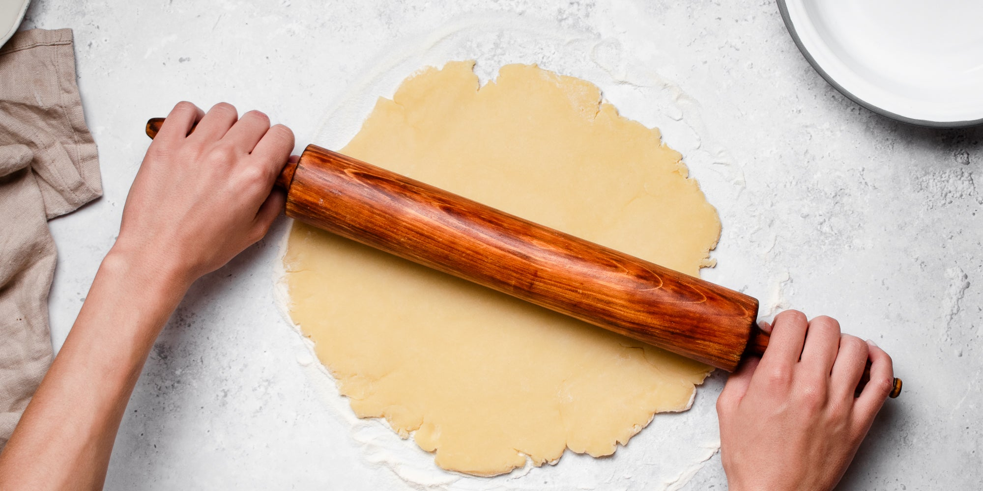 Shortcrust Pastry being rolled out onto a surface with hands holding a wooden rolling pin