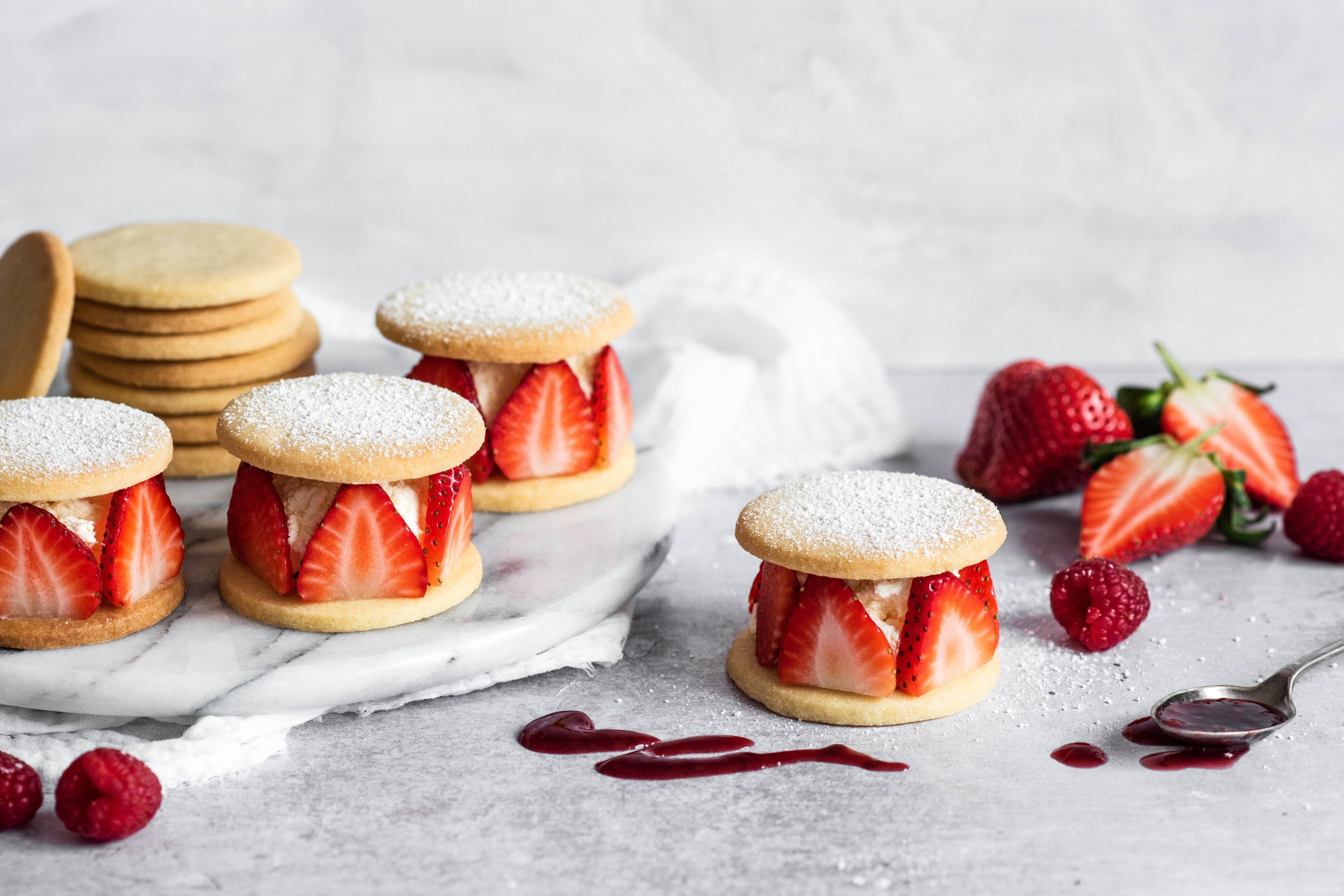 Shortbread rounds with sliced strawberries and cream sandwiched between