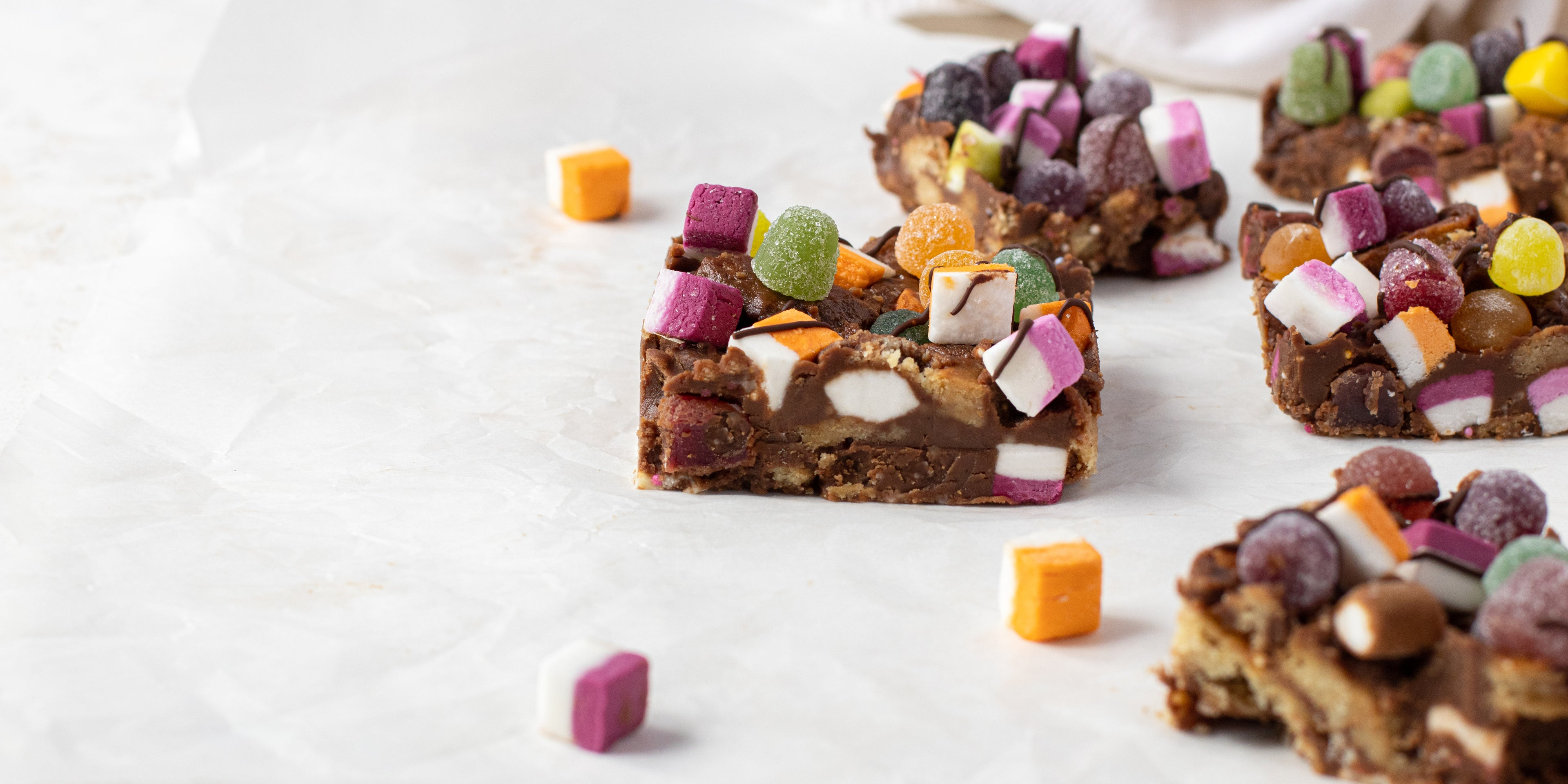 Close up of a slice of Sweetie Rocky Road, topped with dolly mixtures and drizzled with chocolate