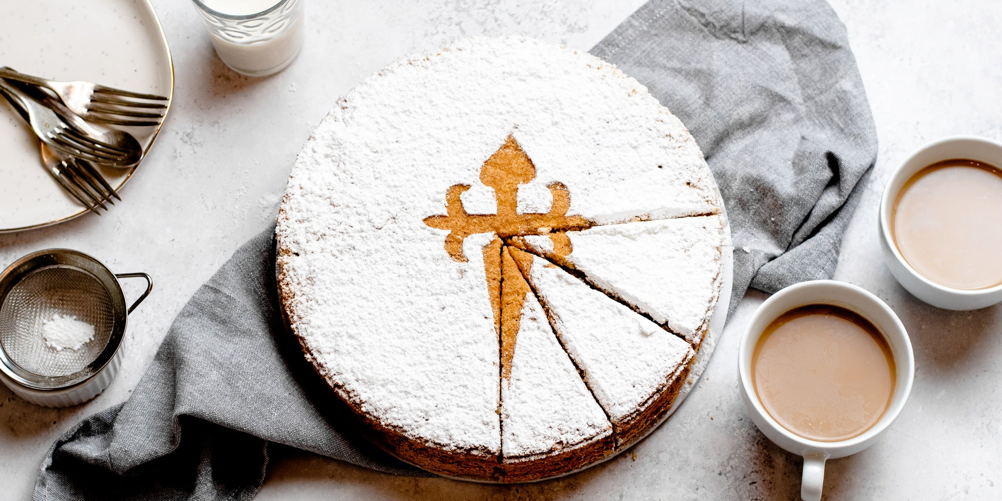 Tarta de Santiago with three slices cut out of it, served on a linen cloth, next to two cups of tea and cutlery ready to serve