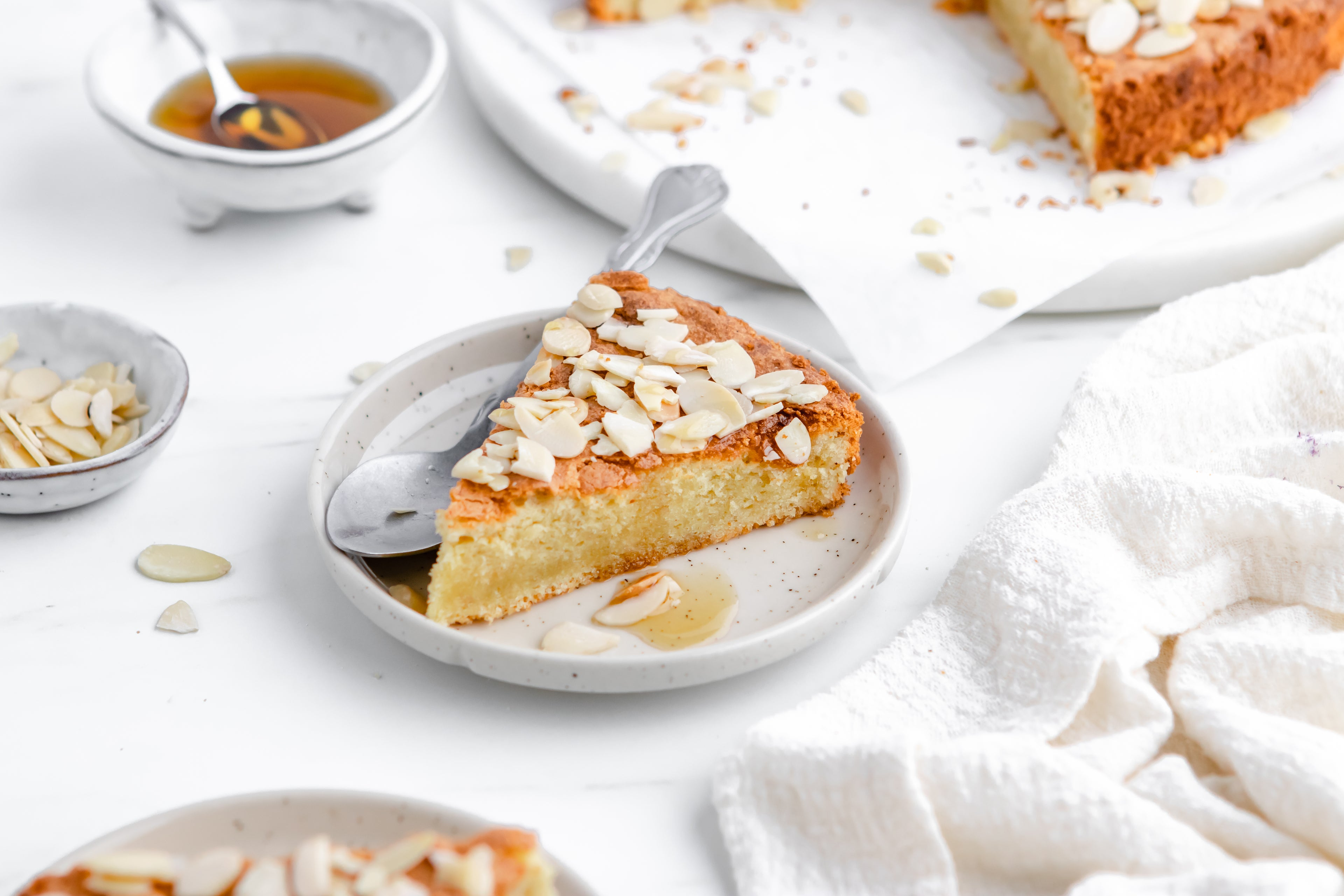 A slice of almond cake on a plate with a spoon