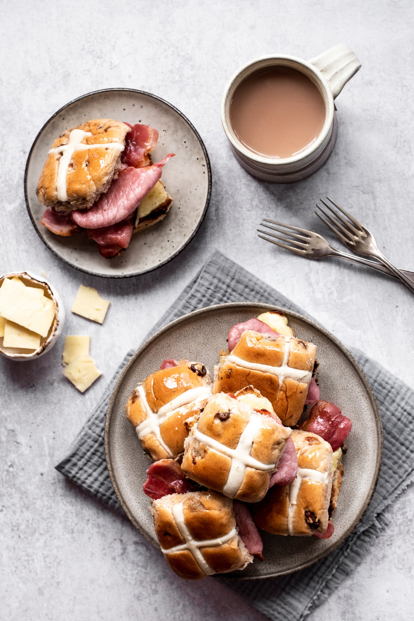 Plate of hot cross buns stacked up. Cup of tea. Two forks. Plate with hot cross bun and bacon