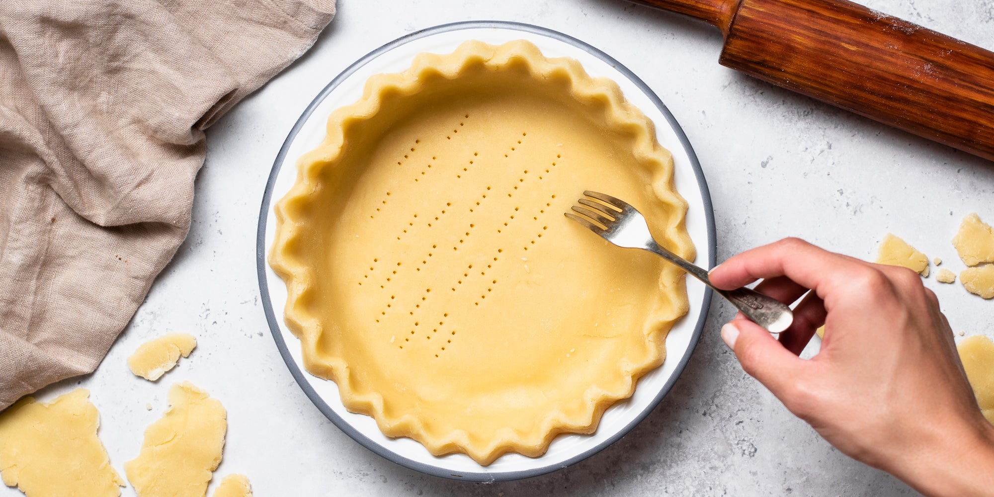 Shortcrust Pastry being pricked with a fork held by a hand, in a pastry tin
