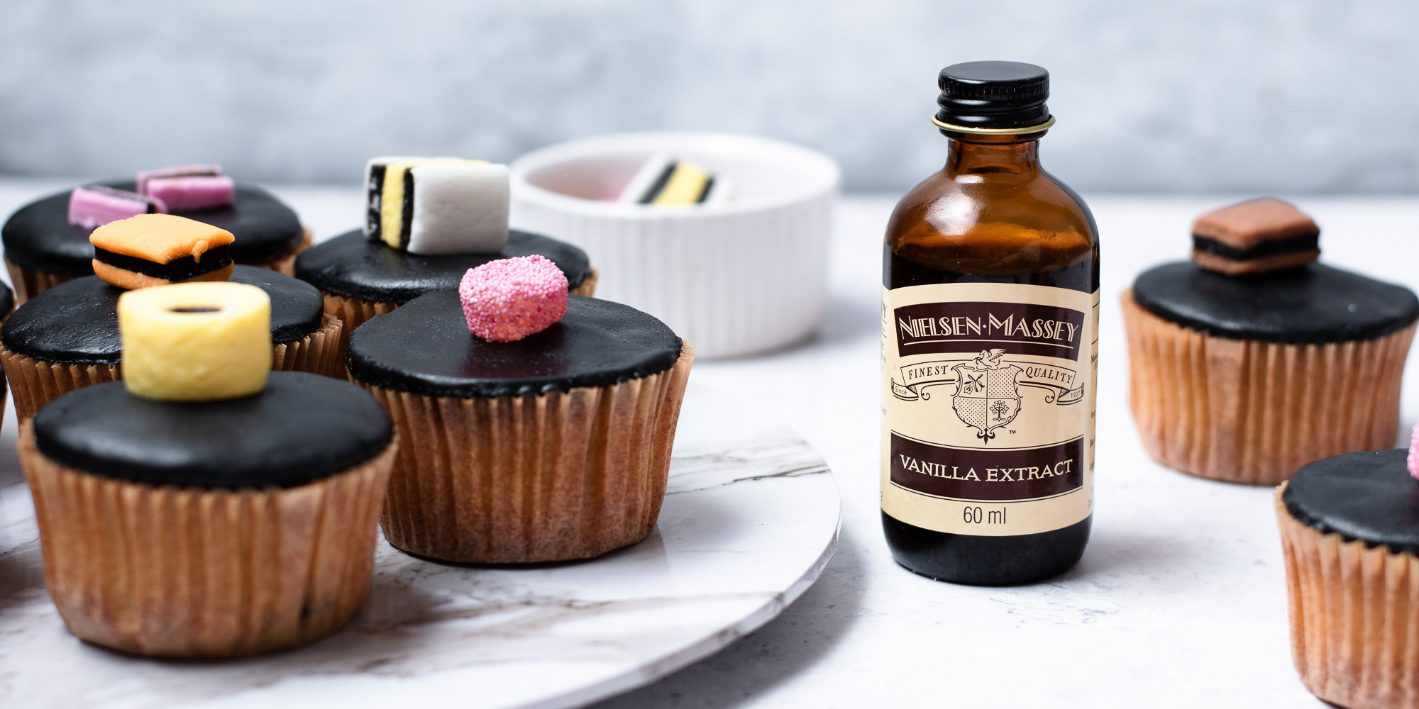 Cupcakes in brown cases, black fondant, topped with liquorice allsorts. Bowl of sweets in background. Vanilla bottle