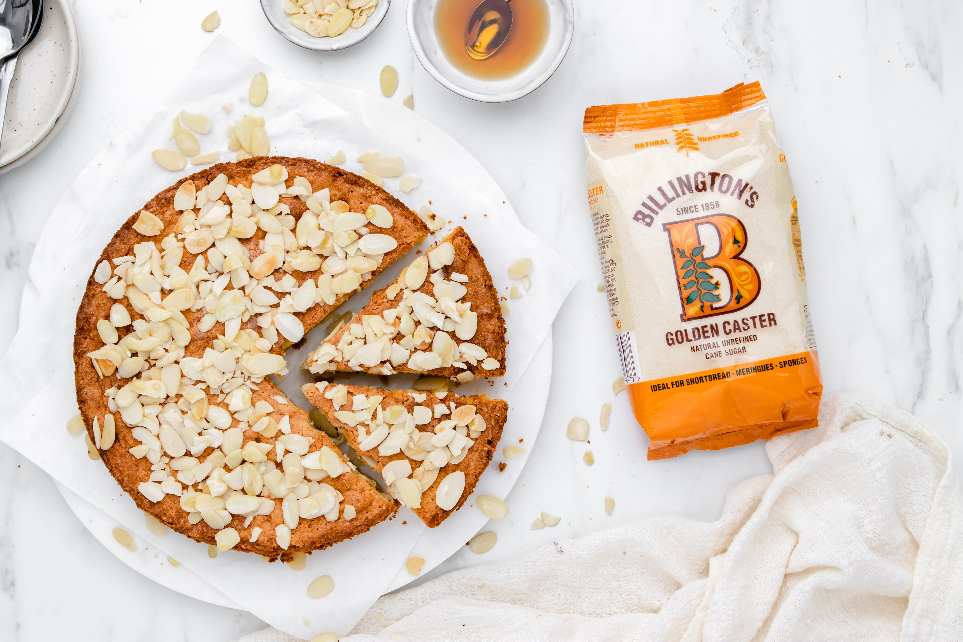 Almond cake with a slice cut out, sprinkled with almonds next to a bag of Billington's Golden Caster sugar