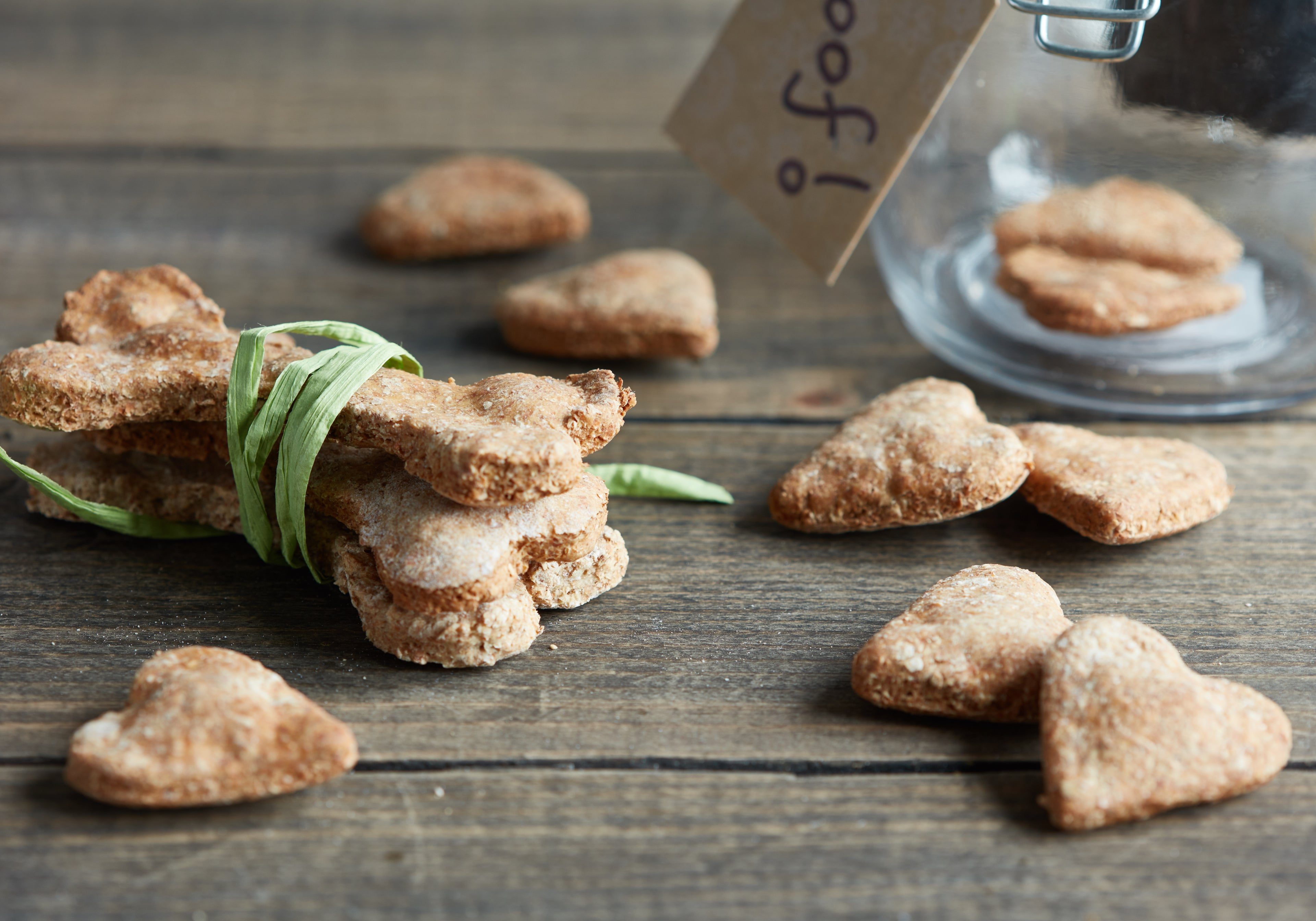 Dog biscuits tied up with ribbon and biscuits scattered around with jar in background