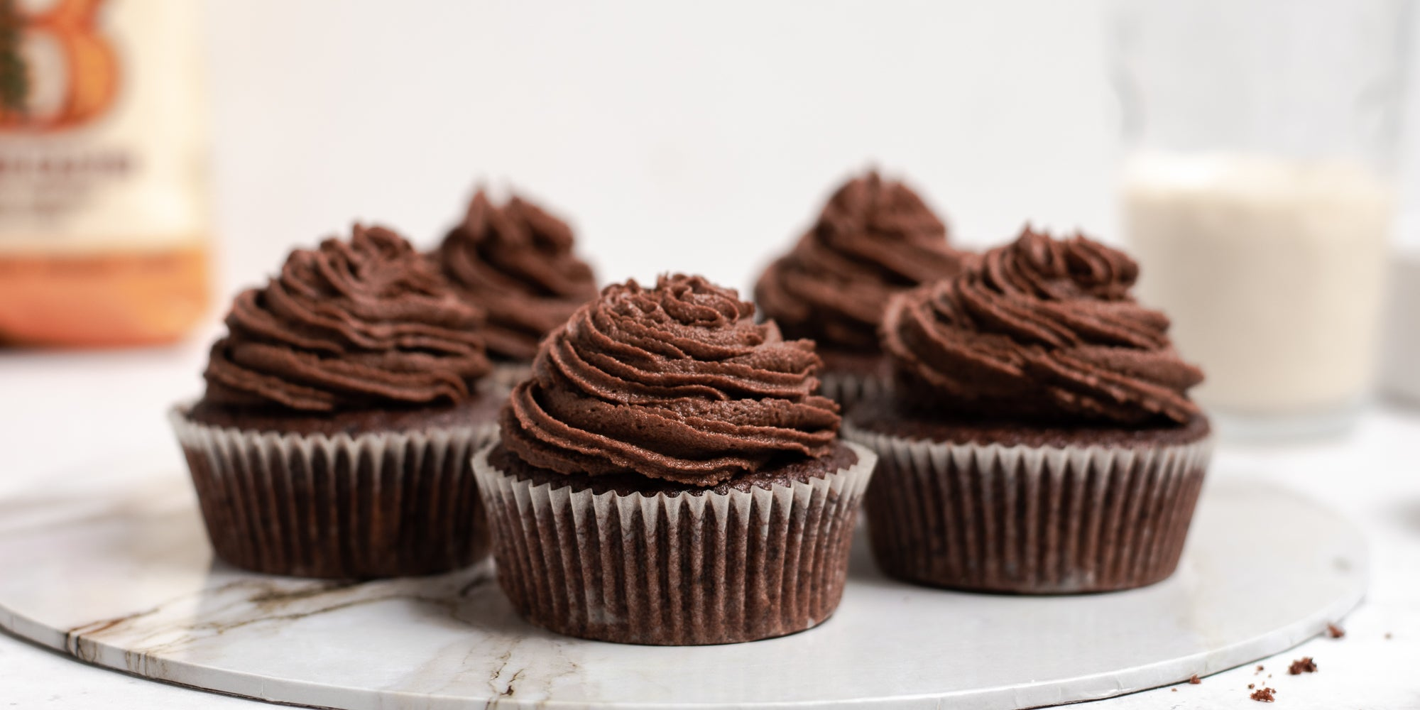 Close up of Vegan Chocolate Cupcakes piped with vegan chocolate buttercream, served on a marble tray