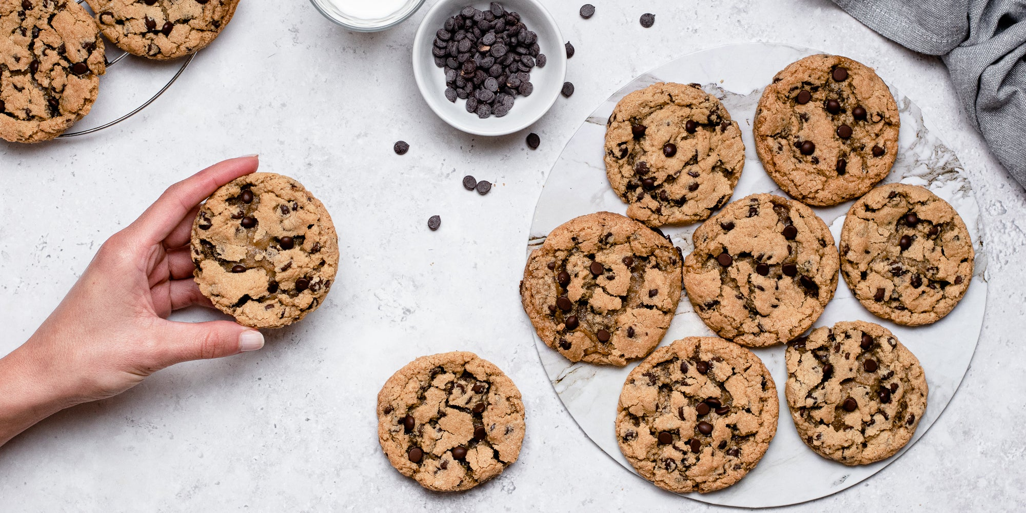 Top down view of a hand holding a vegan and gluten free chocolate chip cookie next to a plate of cookies