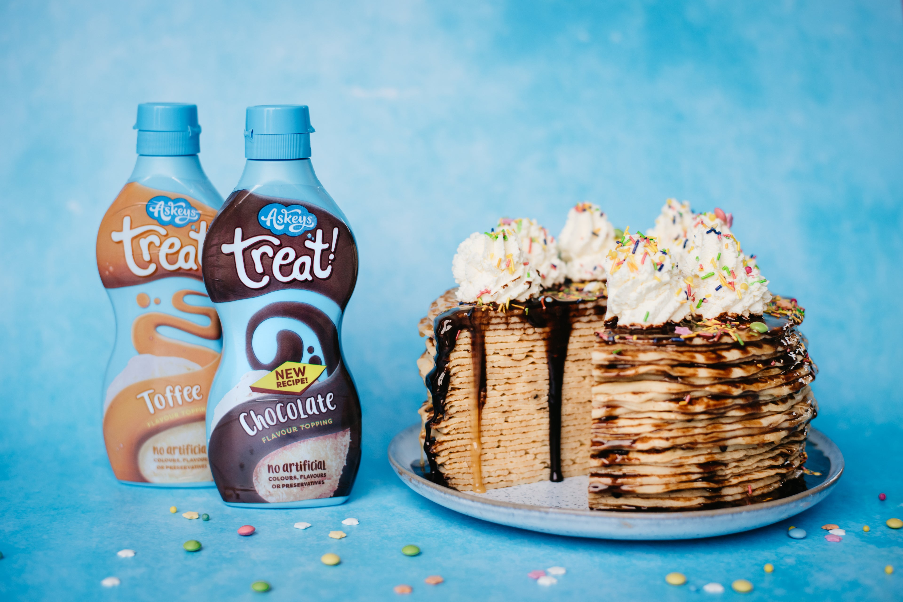 Crepe cake with slice removed, toffee and chocolate treat sauce bottles at side