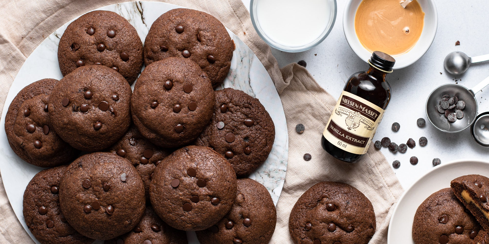 Chocolate & Peanut Butter Stuffed Cookies on a plate next to a bottle of Nielsen-Massey vanilla extract
