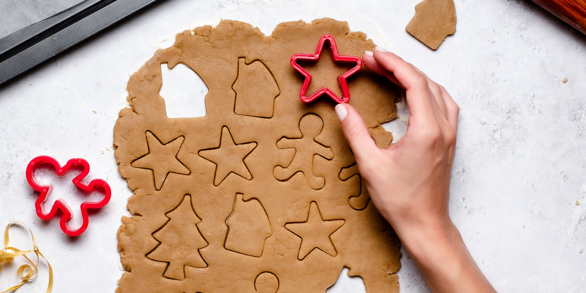 Top down view of a hand using a star cookie cutter to cut out vegan gingerbread dough