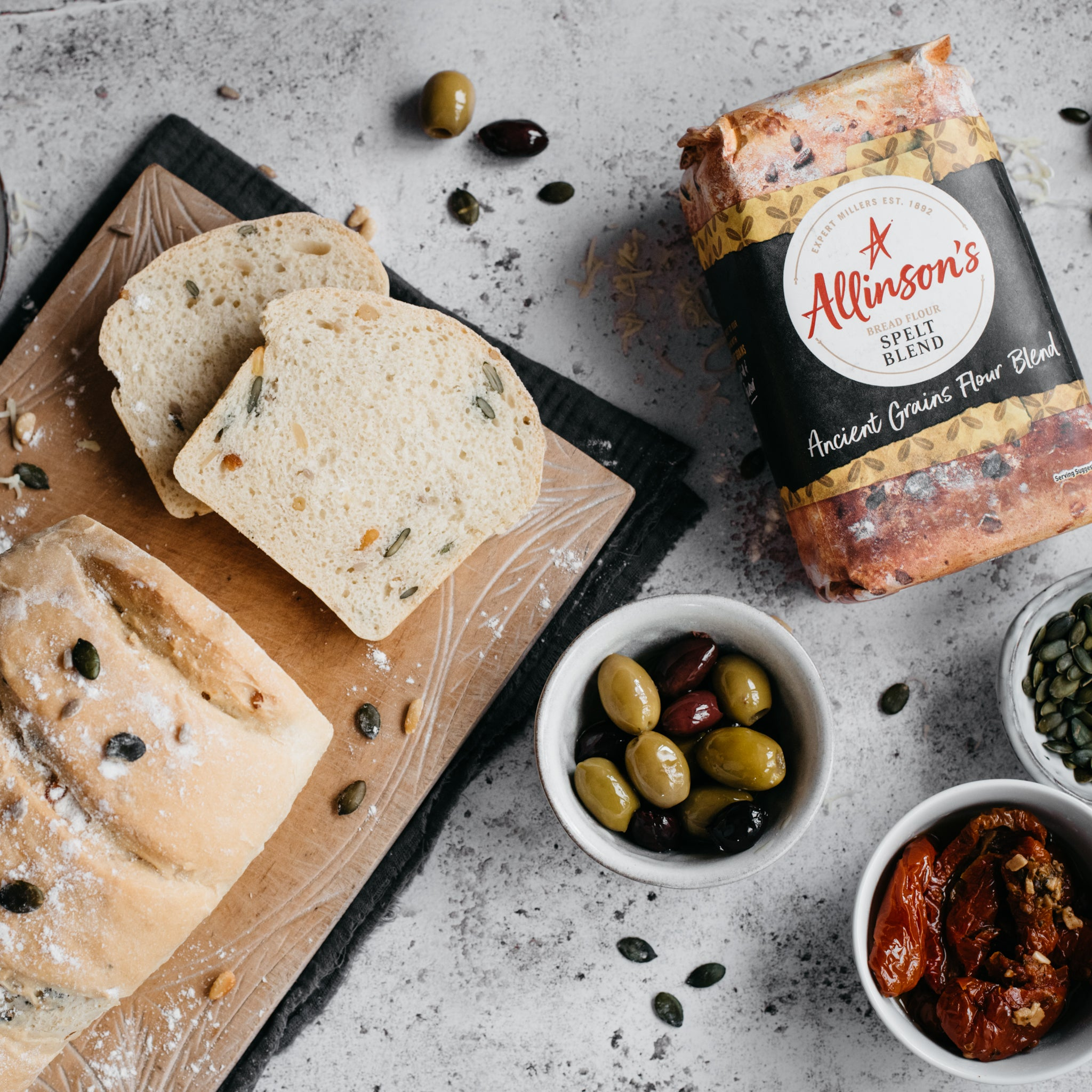 Overhead shot of spelt loaf with two slices in front, bread flour, olives and tomatoes