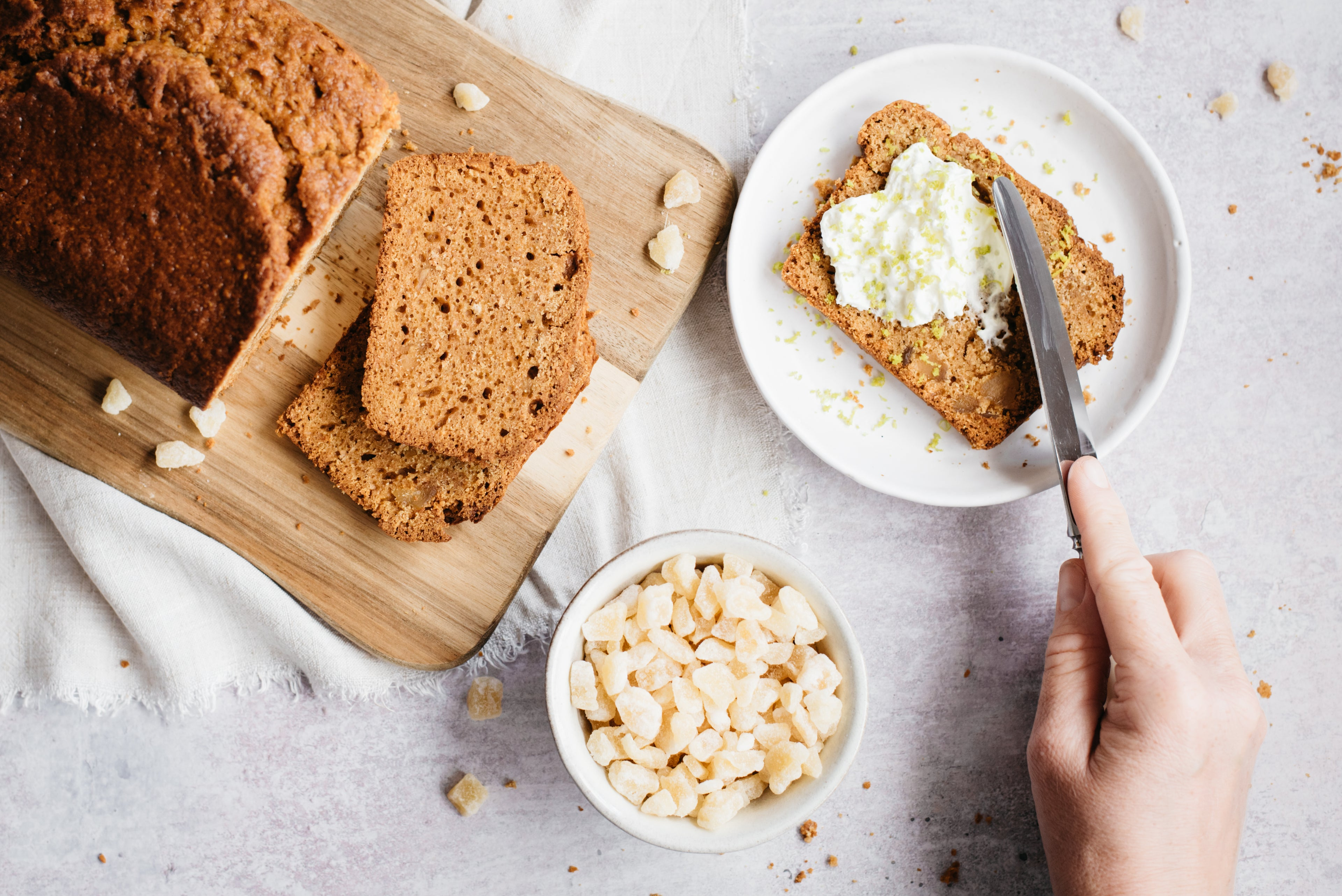 Flat lay of Gingerbread Loaf on a serving board, next to a bowl of ginger and a plate with a slice of Gingerbread Loaf with a hand buttering it