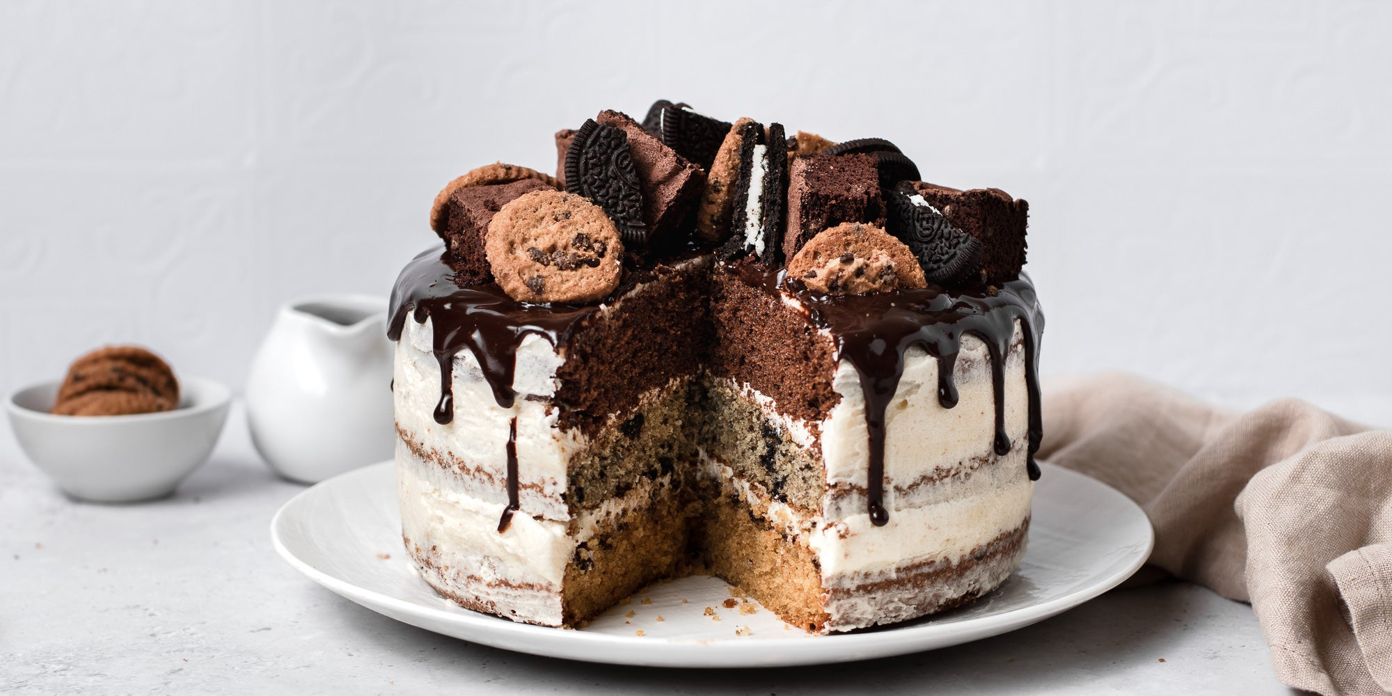 Cookie, Oreo & Brownie Layered Cake with a slice cut out of it.