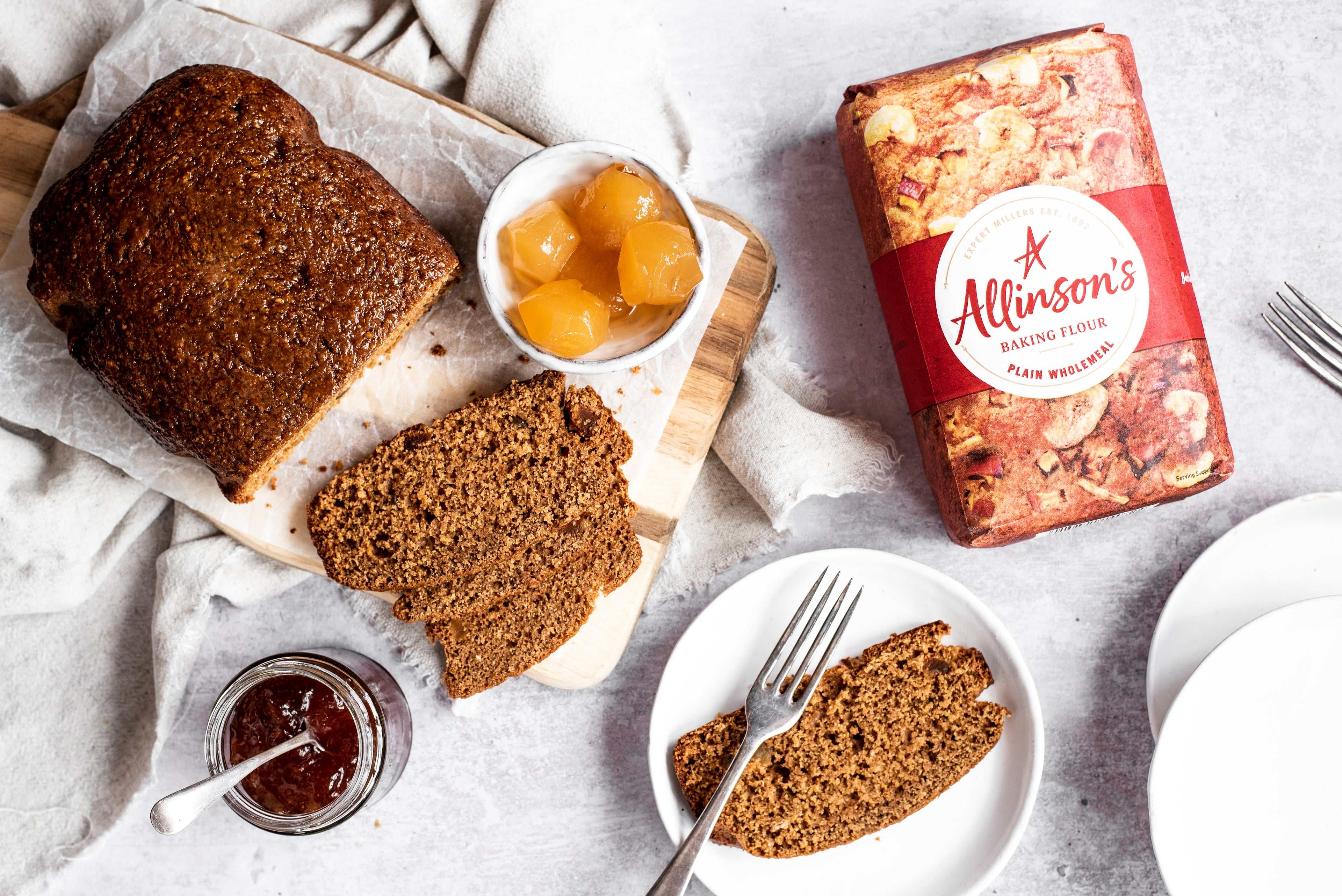 Overhead shot of gingerbread loaf with slices cut in front. Slice of cake on plate with fork. Bowl of ginger. Marmalade jar. Flour pack