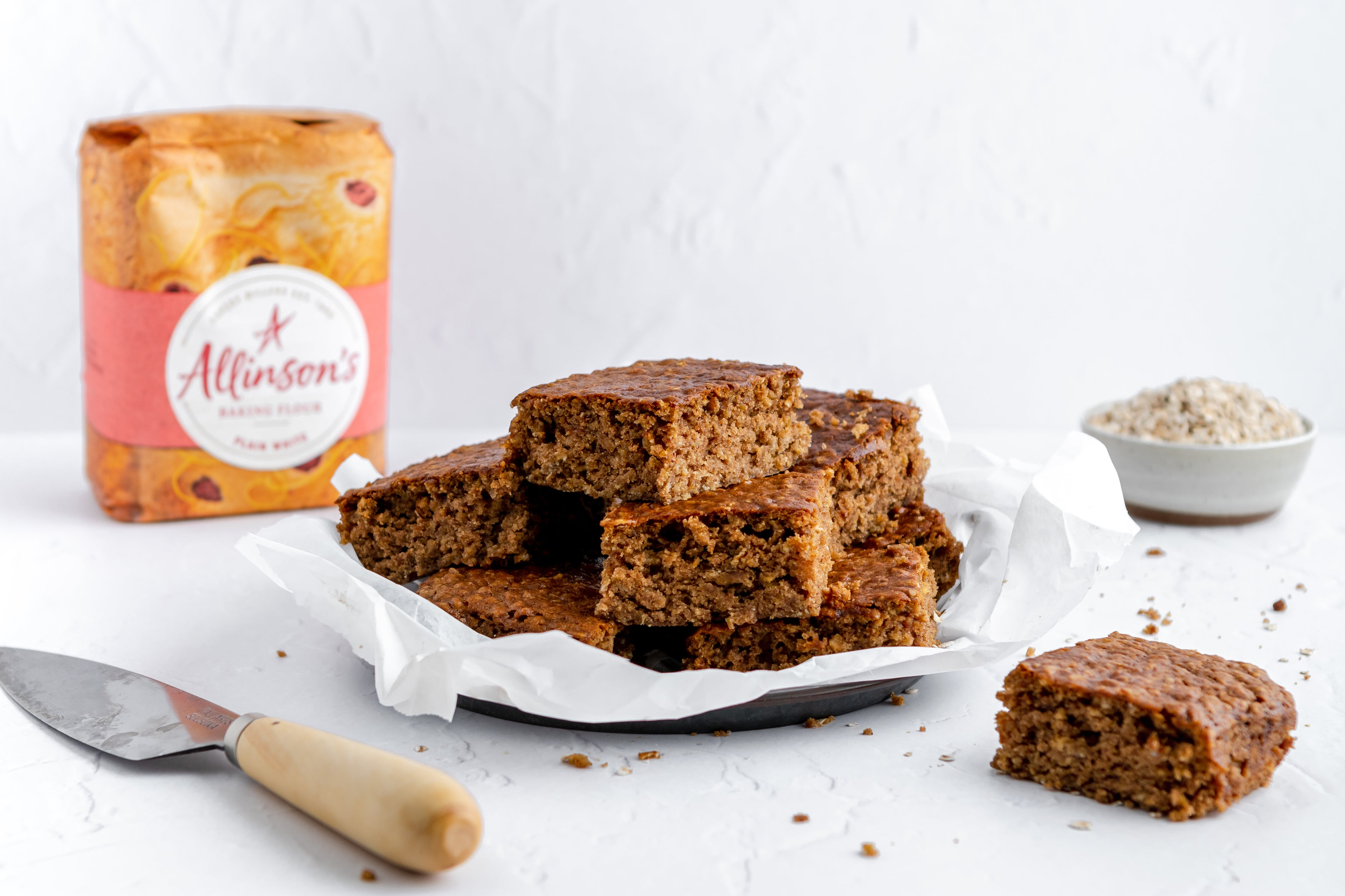 Sticky Yorkshire Parkin slices next to Allinson's Plain White flour, and a cake knife
