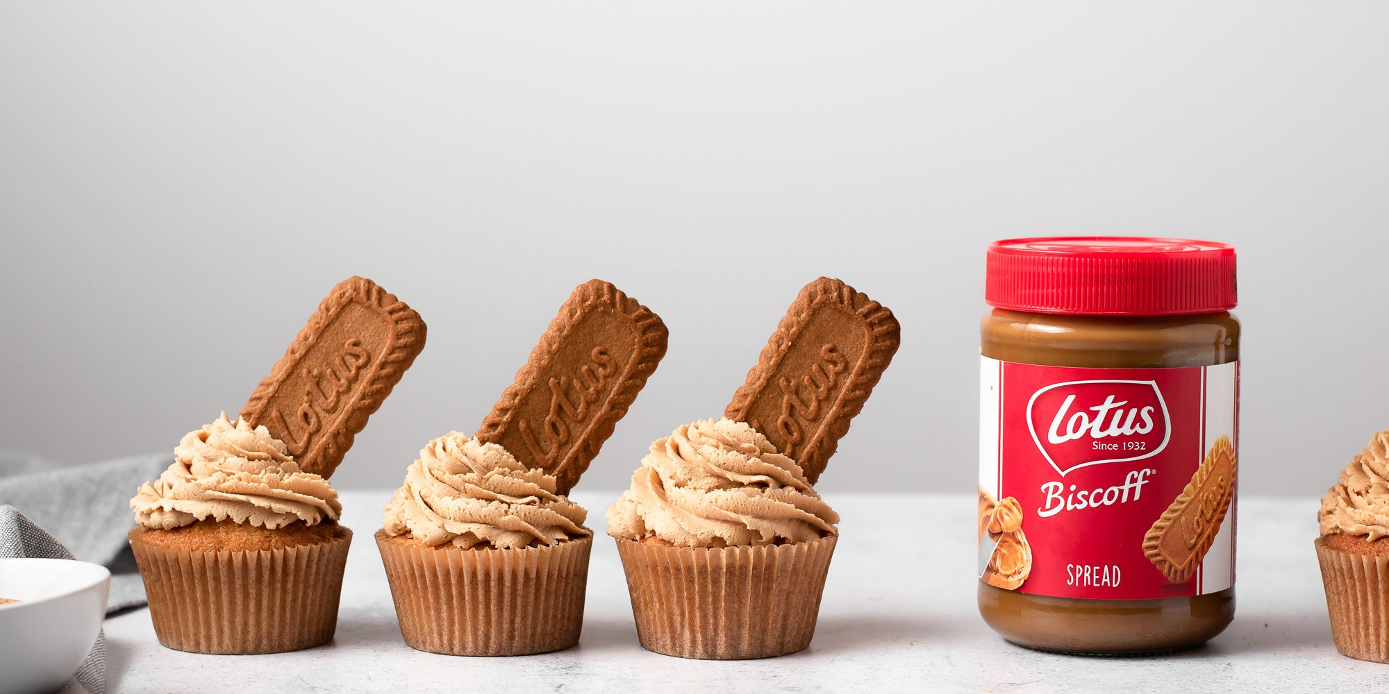 four Biscoff cupcakes next to jar of Lotus Biscoff spread