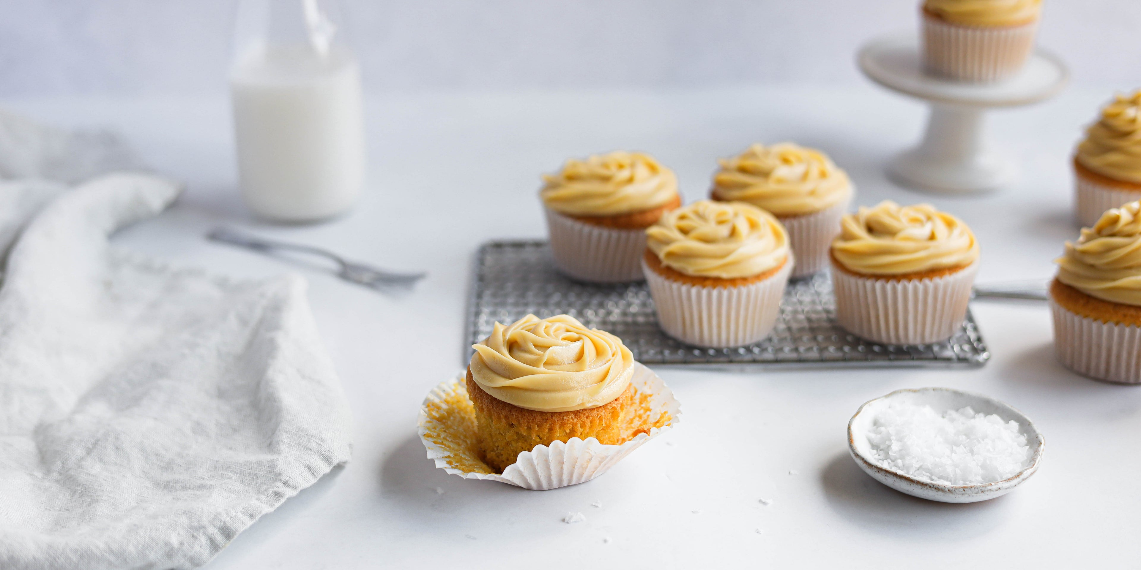 Salted Caramel Cupcakes on a wire rack, side dish of rock salt and white cloth with fork ready to serve