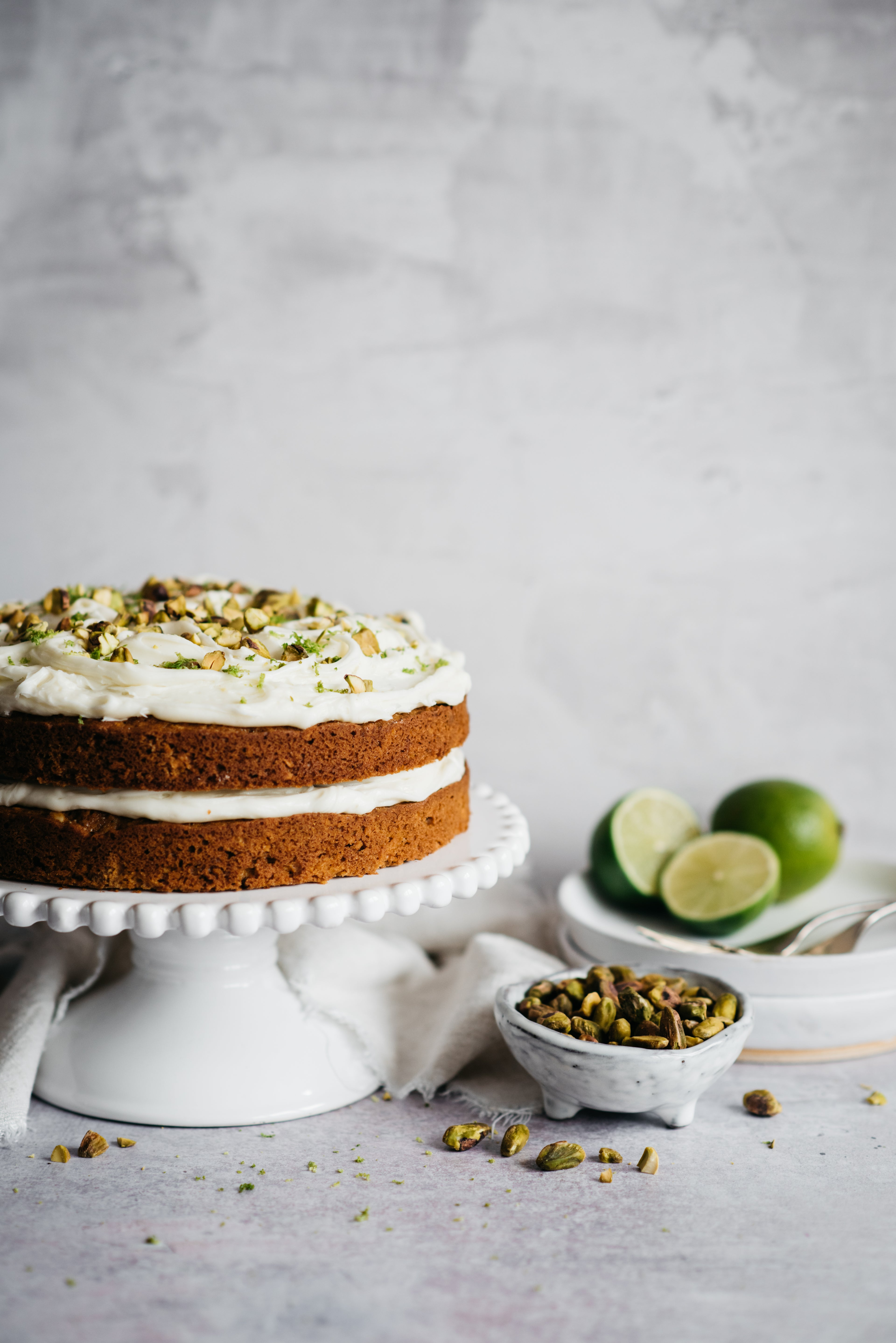 Carrot cake with icing on cake stand. Bowl of pistachios and limes in foreground