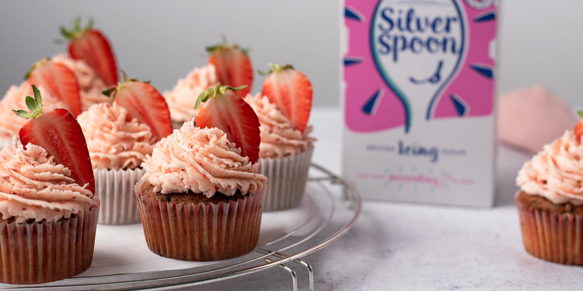 Strawberry cupcakes on a plate topped with strawberry buttercream