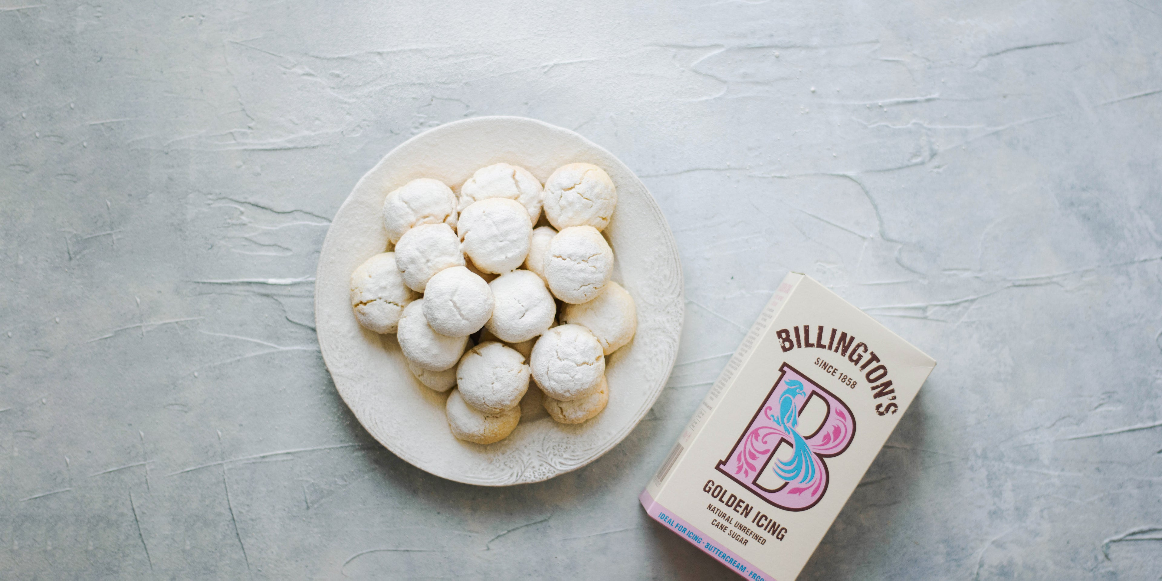 Kahk Eid dusted with golden icing sugar, next to a flat lay box of Billington's icing sugar