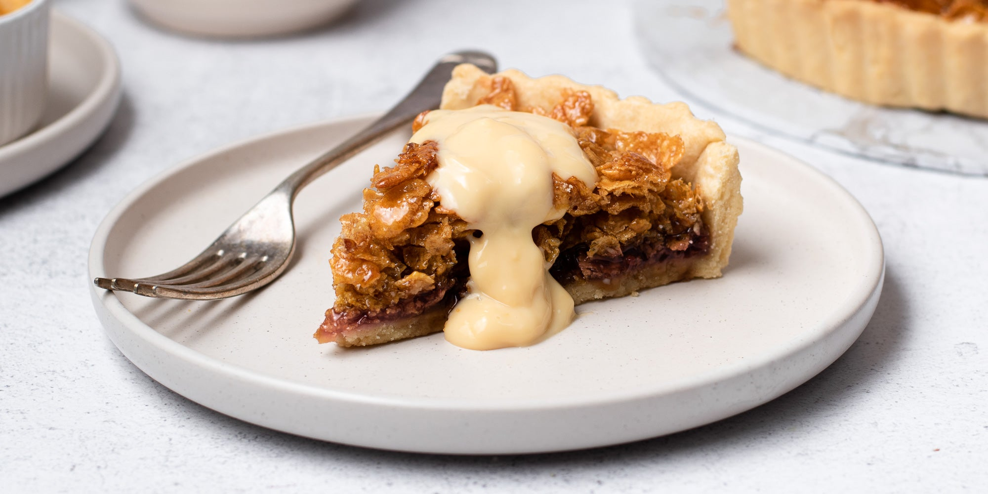 Cornflake Tart with custard on a plate with fork