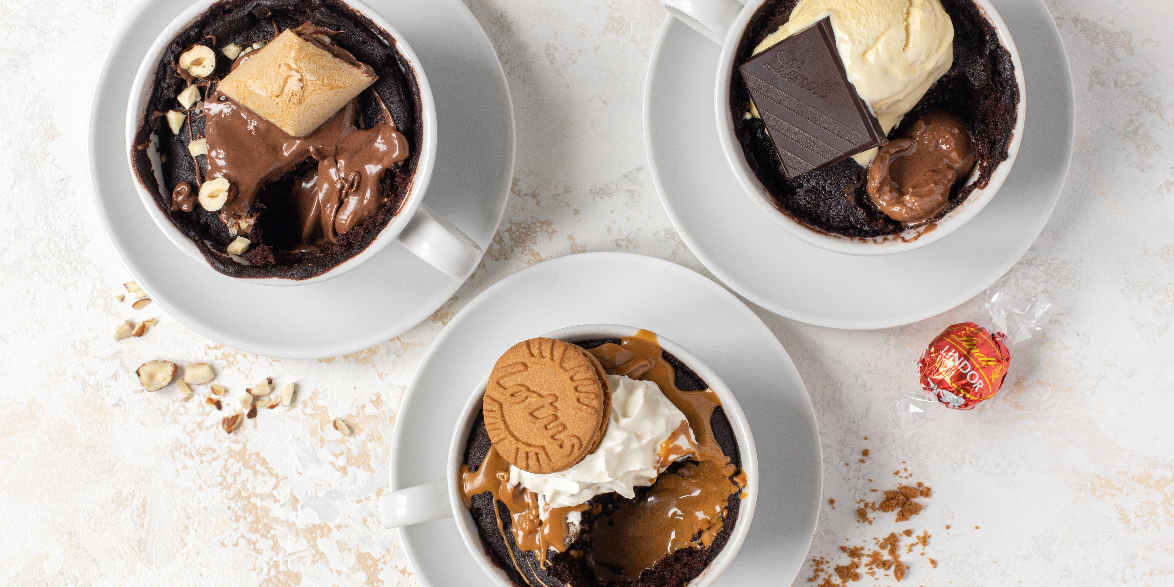 Top view of Chocolate Mug Cakes customised with Nutella, Lindt and Lotus Biscoff, with a Lindt ball and biscuit crumbs