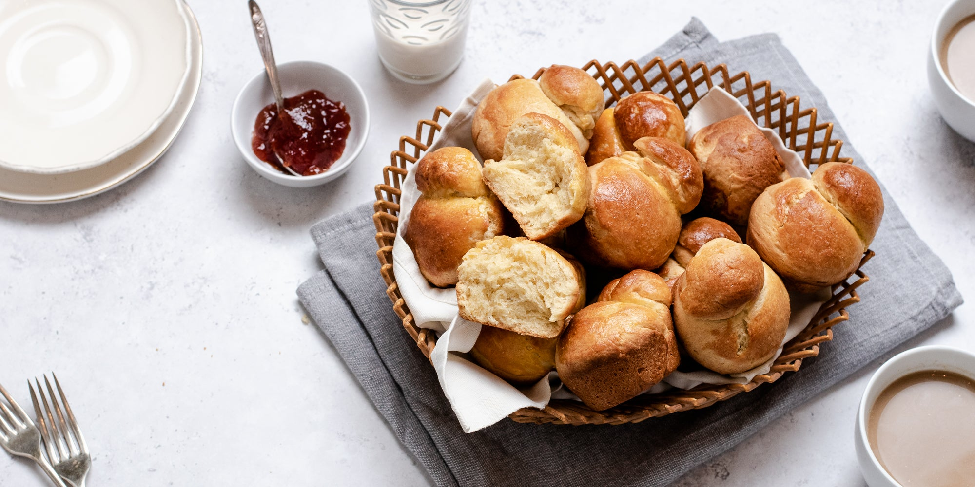 Basket of fresh Brioche, with one torn apart showing the fluffy inside. Next to a small bowl of jam with a spoon