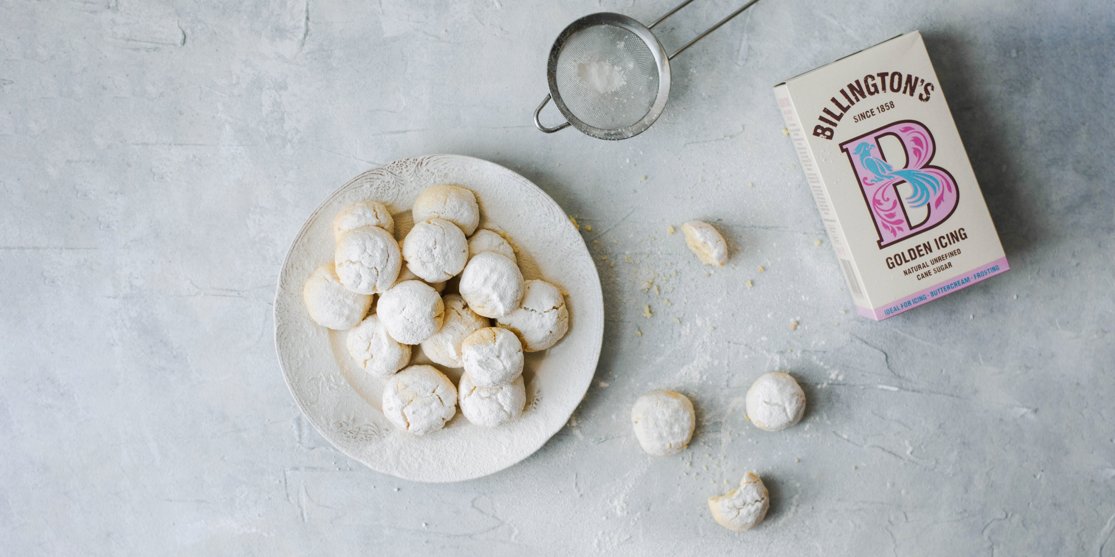 Kahk Eid on a plate with sieve and box of Billington's golden icing sugar