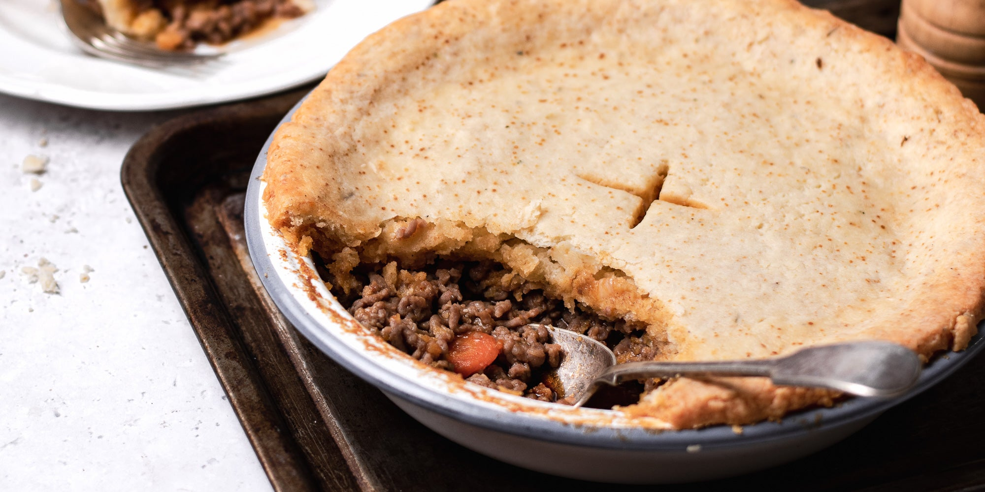 Close up of Suet Crusted Beef & Onion Pie, with the crust open and the filling being scooped out by a serving spoon. Pie is served on a baking tray