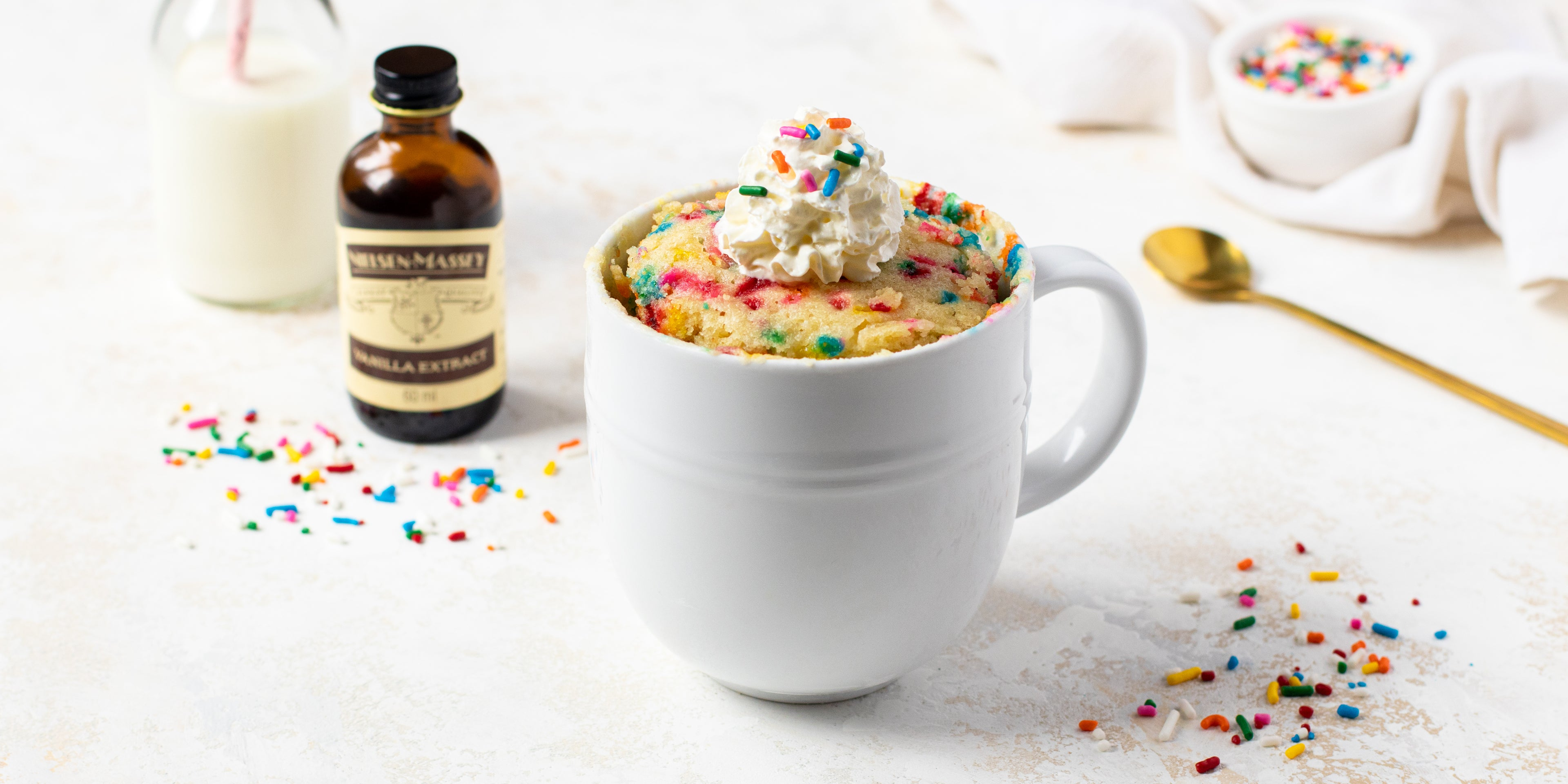 Birthday Cake Mug Cake with a dollop of whipped cream on top with sprinkles, and a bottle of Nielsen-Massey Vanilla extract in the background