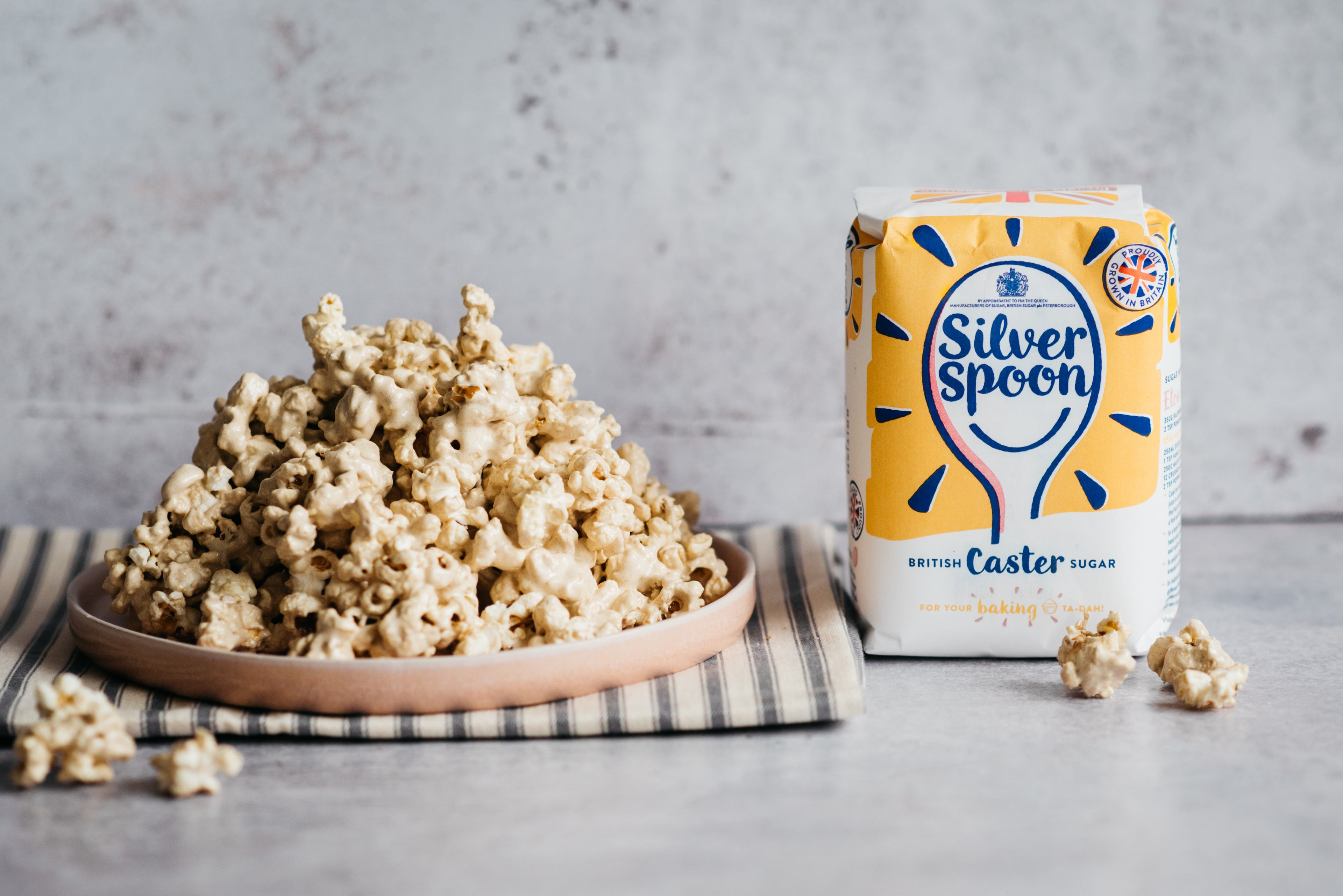 high pile of marshmallow popcorn on a plate with a pack of sugar next to it