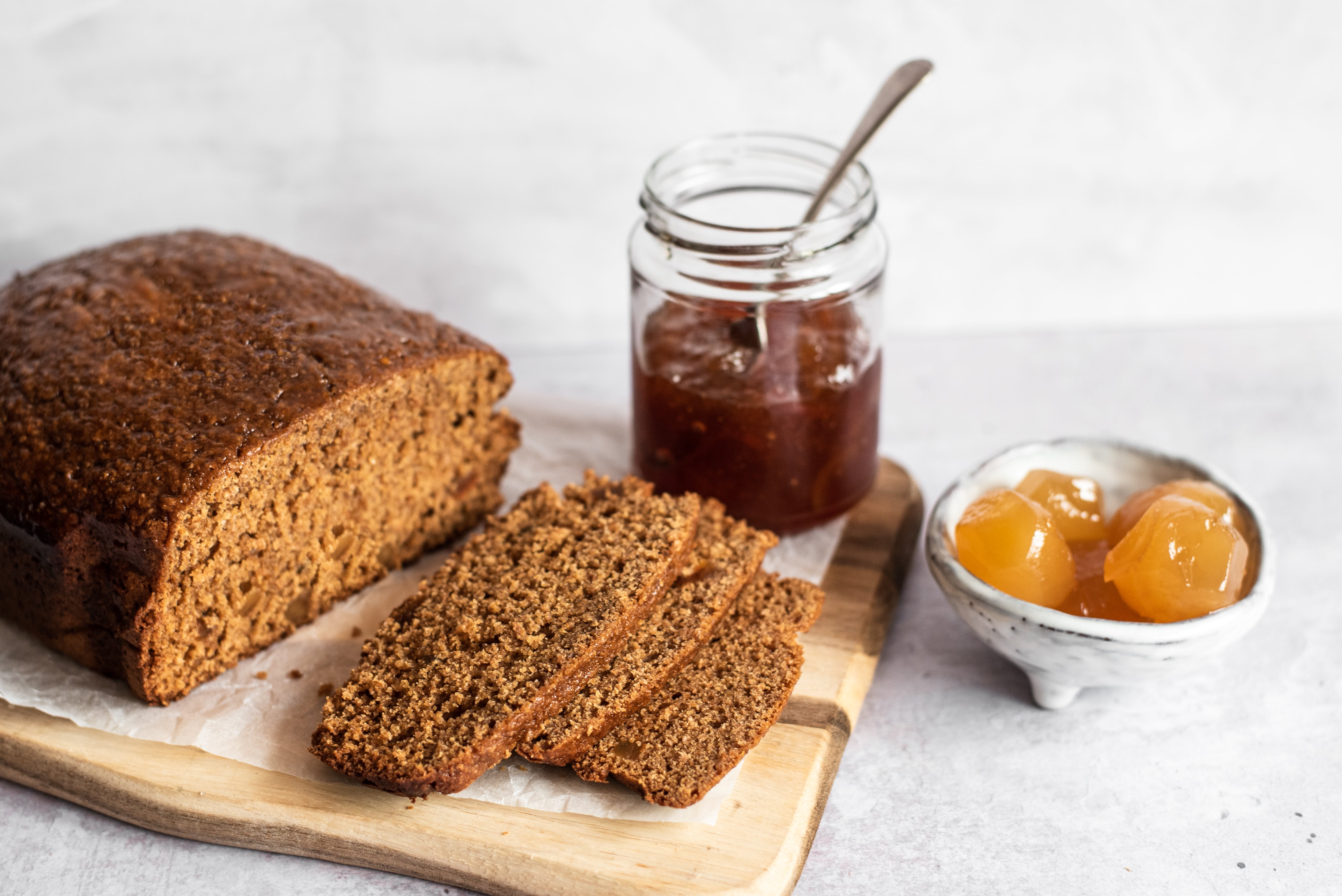 Gingerbread loaf on bread board, three slices infront, ginger in bowl and marmalade