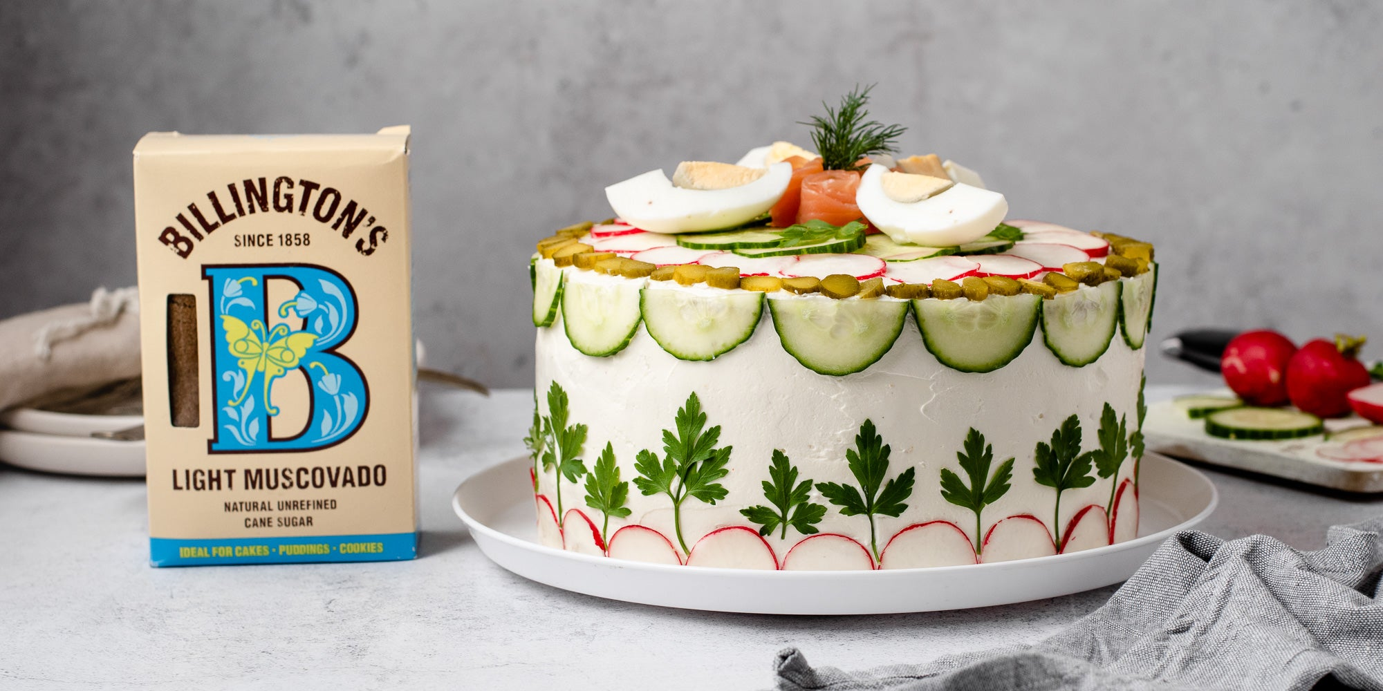 Full shot of savoury cake on white plate with pack of sugar