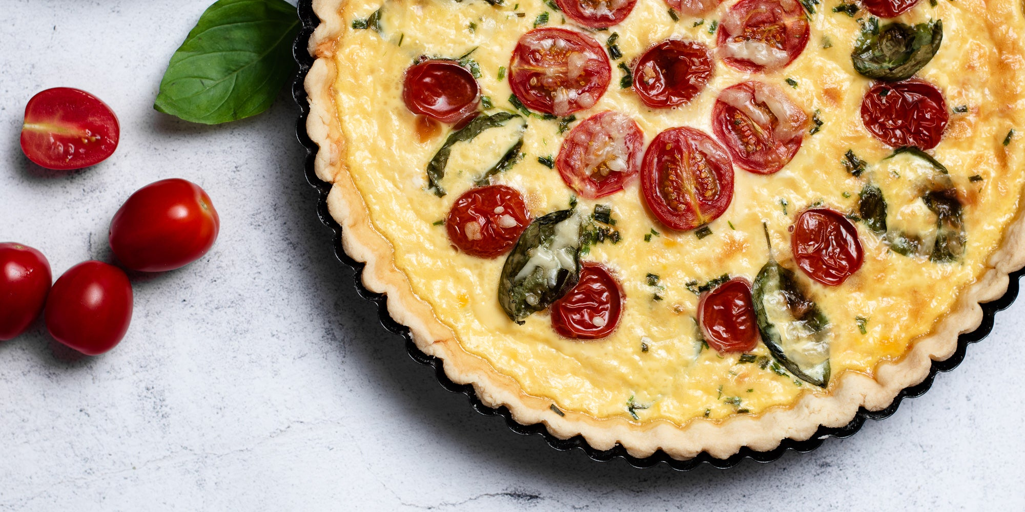 Close up of a Cheese & Tomato Quiche with whole tomatoes and a basil leaf in a pastry baking tray