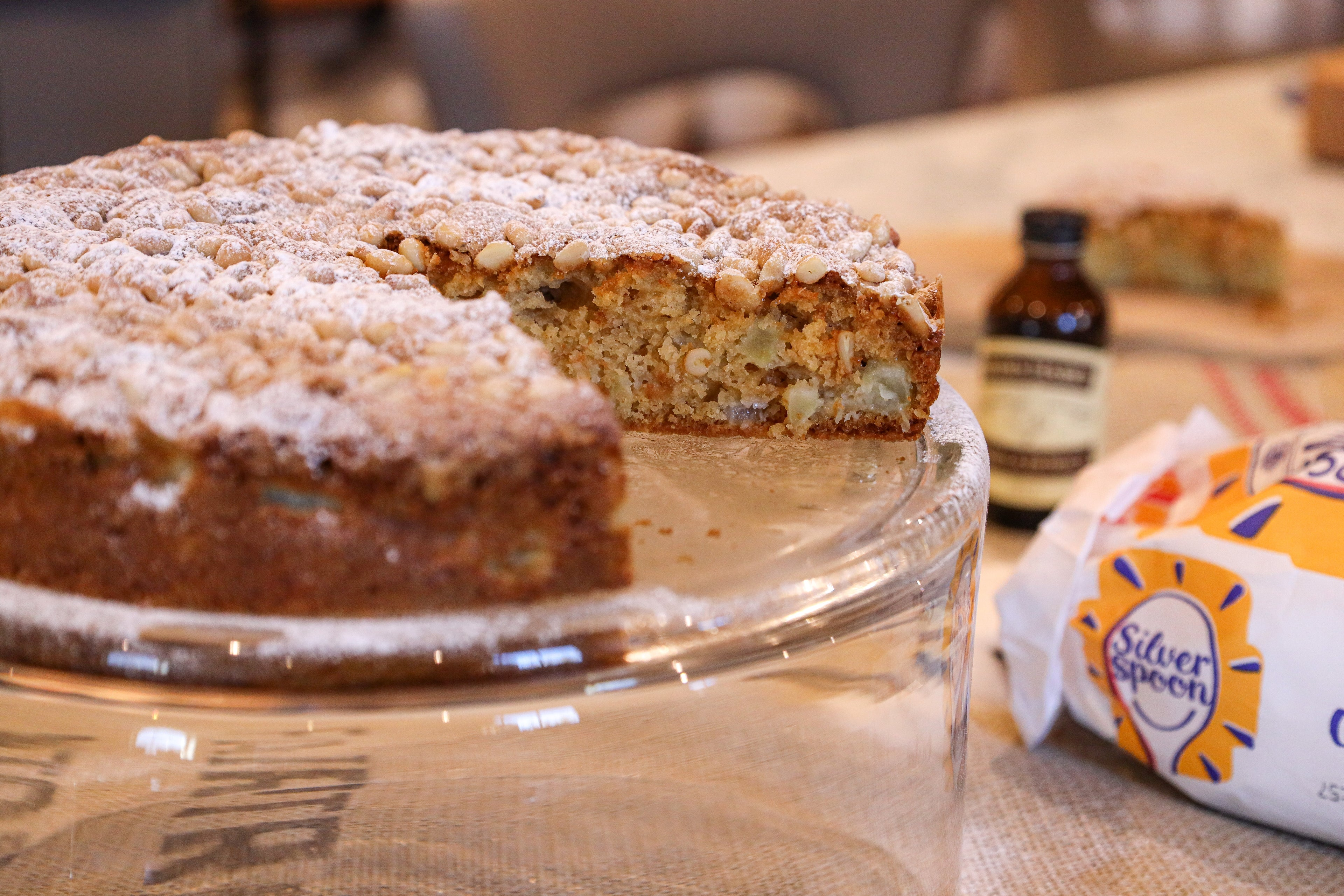 Apple cake with slice cut out, sugar pack and vanilla bottle in background