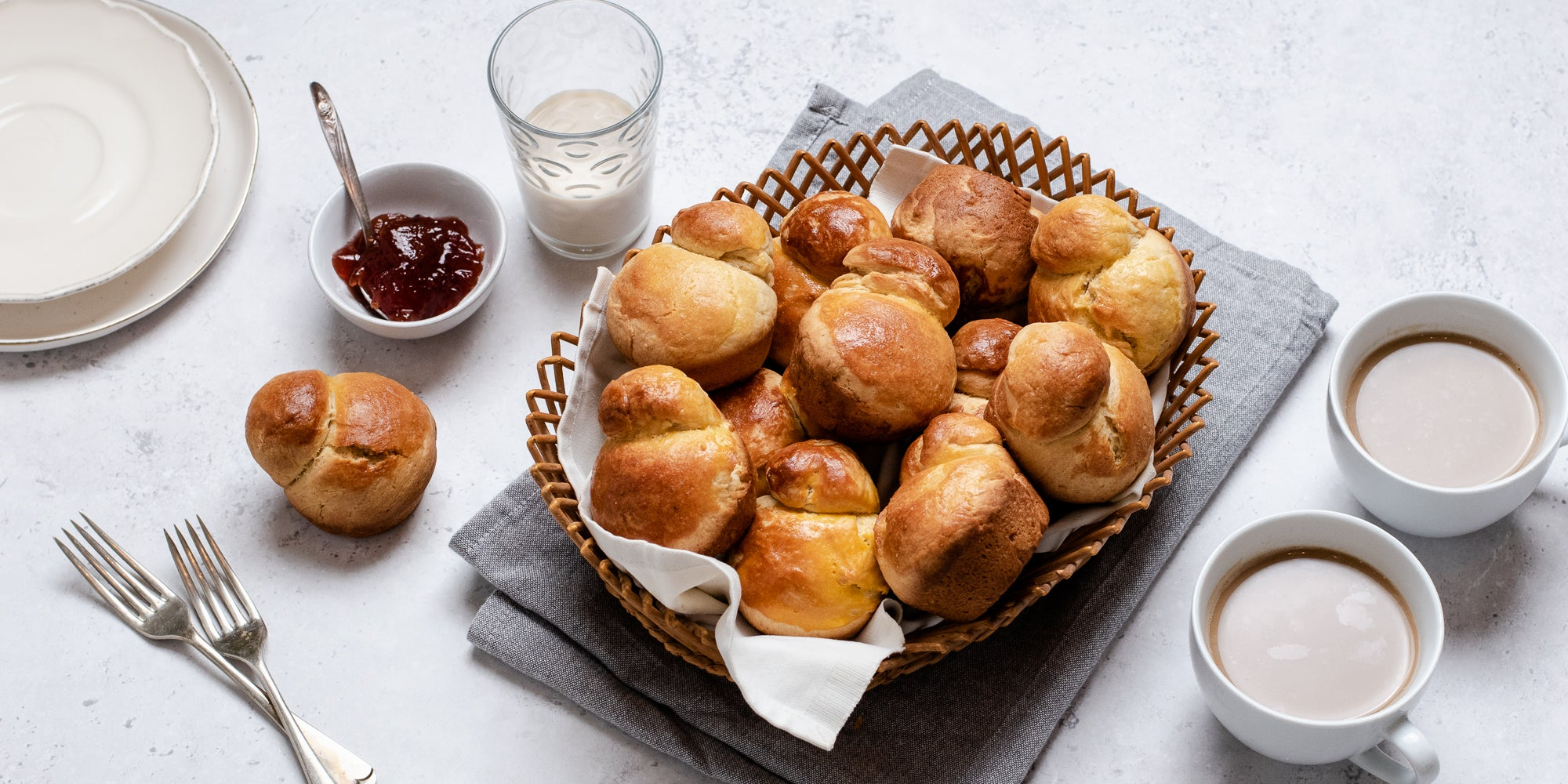 A batch of golden Brioche in a wicker basket, next to cups of tea, a bowl of jam and a glass of milk