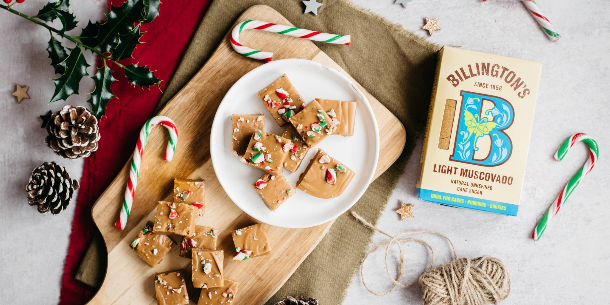 Top view of Billington's Candy Cane Fudge, on a wooden board next to candy canes, pine cones and a box of Billington's Light Muscovado sugar