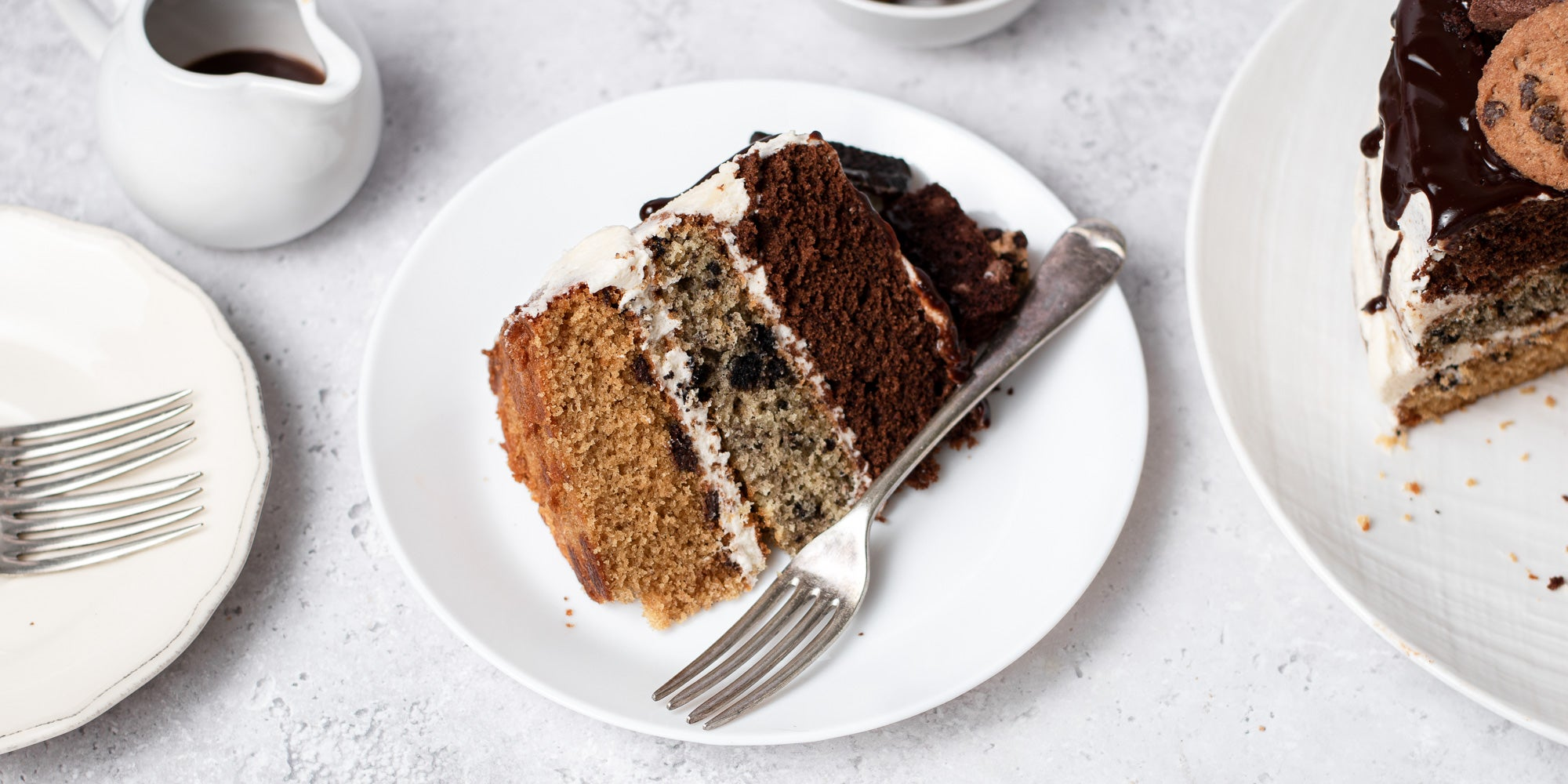Cookie, Oreo & Brownie Layered Cake slice, on a plate with a fork and a small jug of chocolate ganache