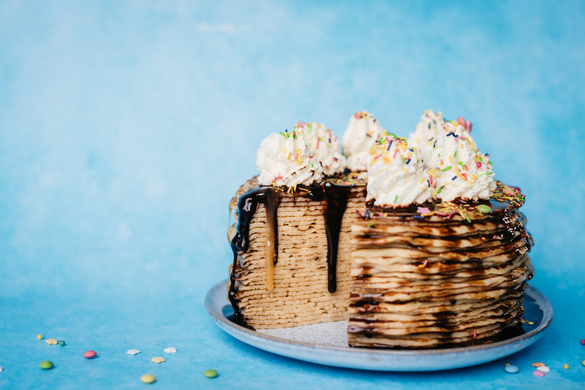 Crepe Cake with slice removed, covered in chocolate and toffee sauce, topped with whipped cream and sprinkles