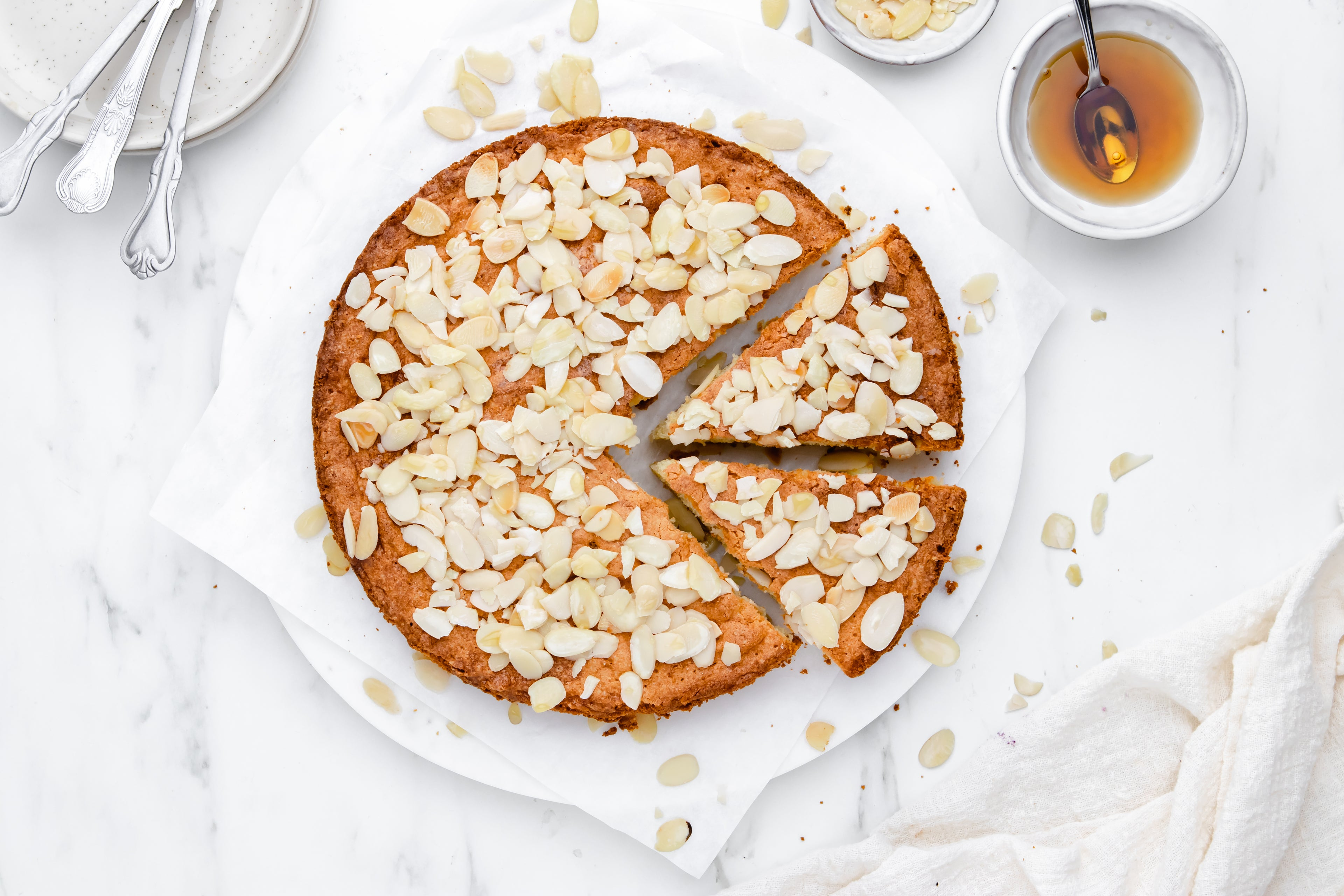 Almond cake with two slices cut out, sprinkled with almonds