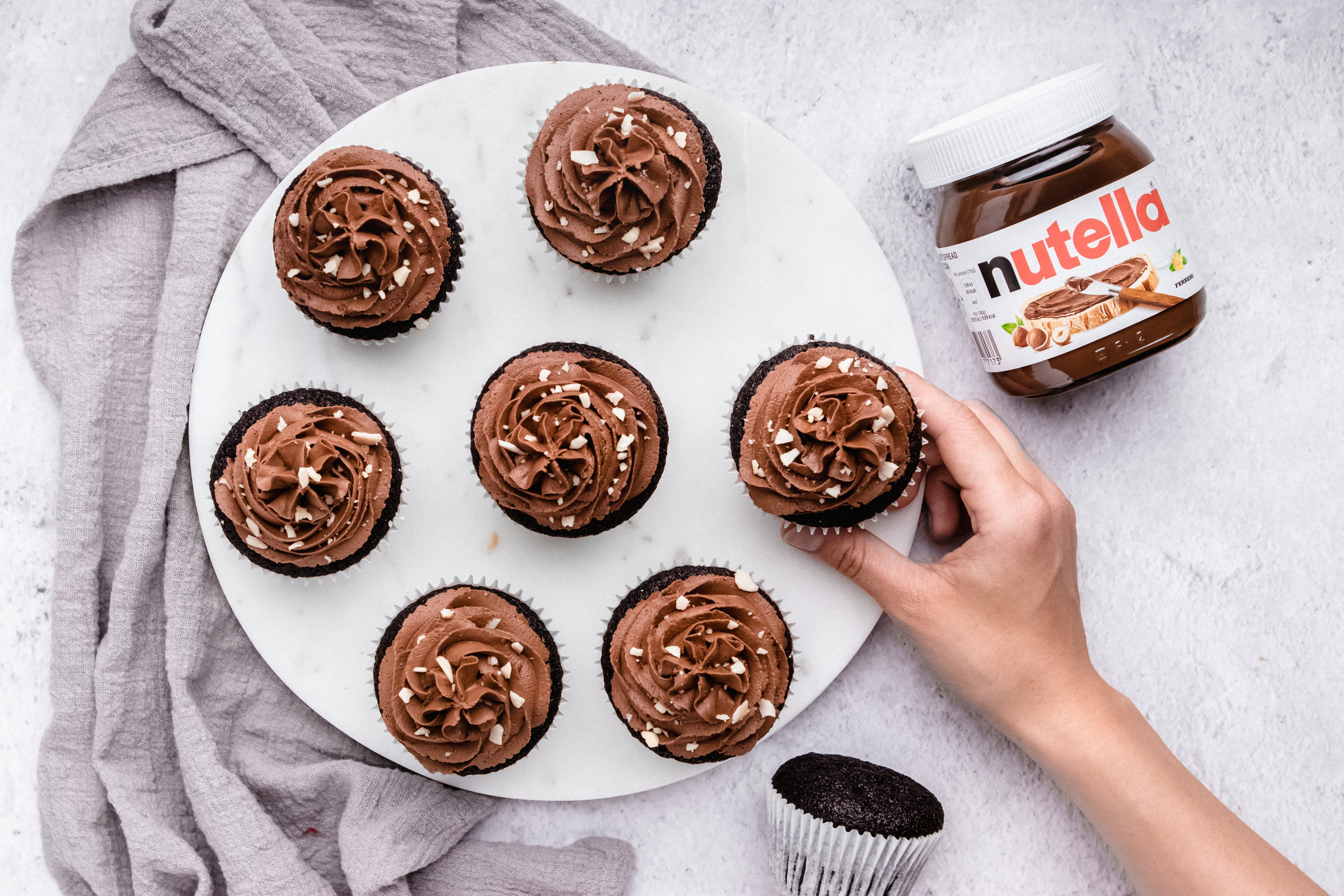 Nutella Cupcakes from above, with hand holding a cupcake next to a jar of Nutella