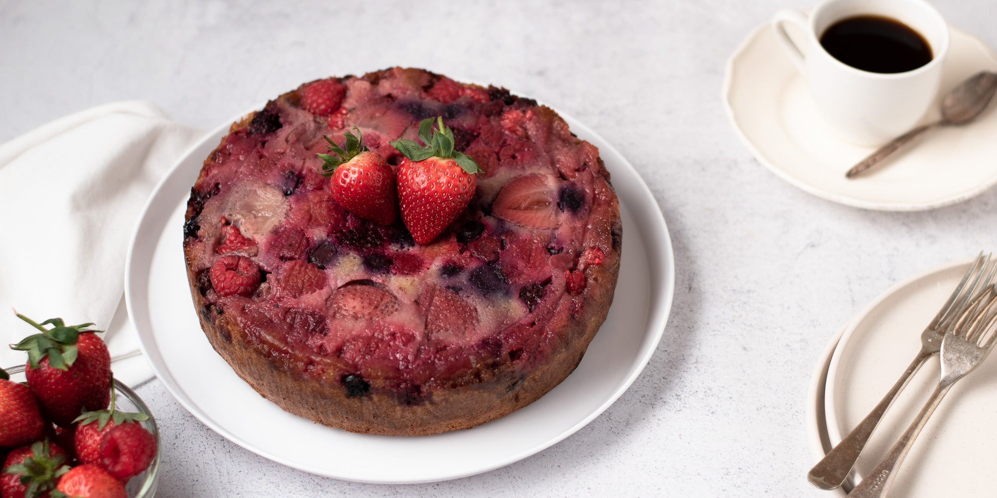 upside down berry pudding on a plate topped with two strawberries