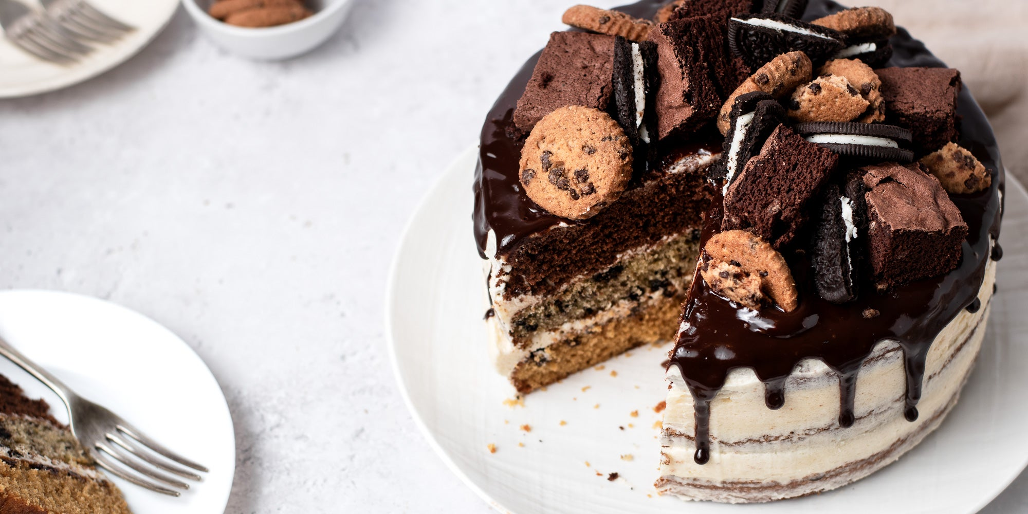 Cookie, Oreo & Brownie Layered Cake with a slice cut out of it, next to a plate with a fork ready to serve