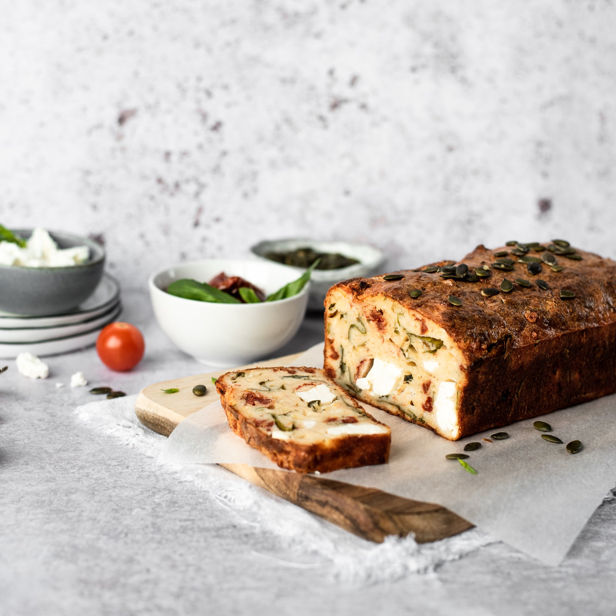 Feta and tomato loaf with slice removed on a chopping board