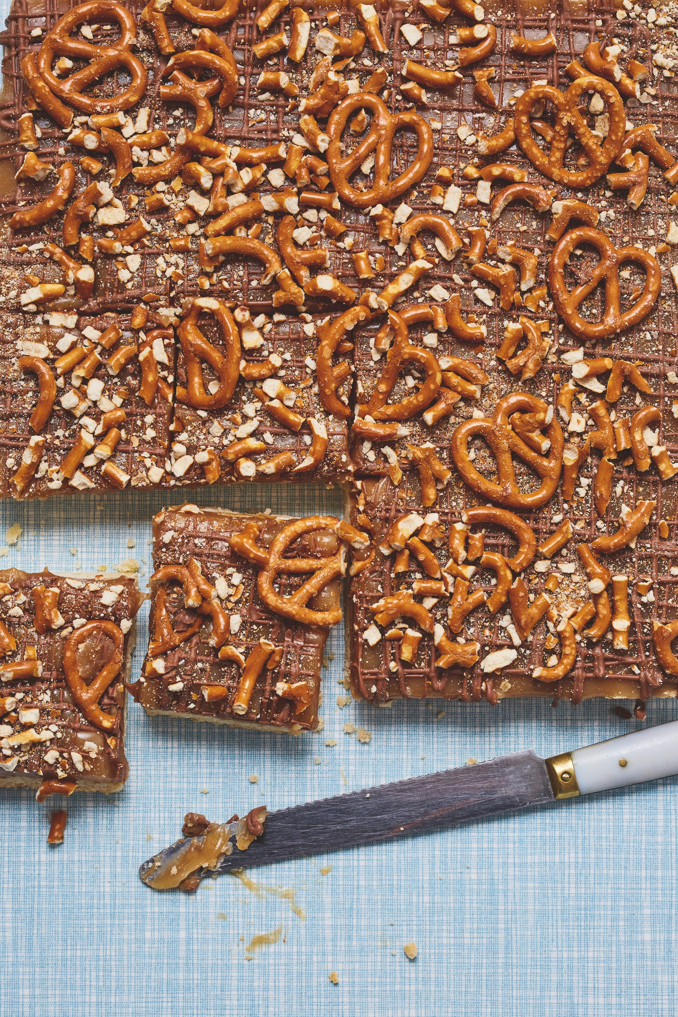 Flat lay of salted caramel pretzel slice with a knife, cuttings into squares